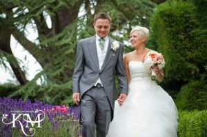 Fawsley Hall wedding - couple walk in garden