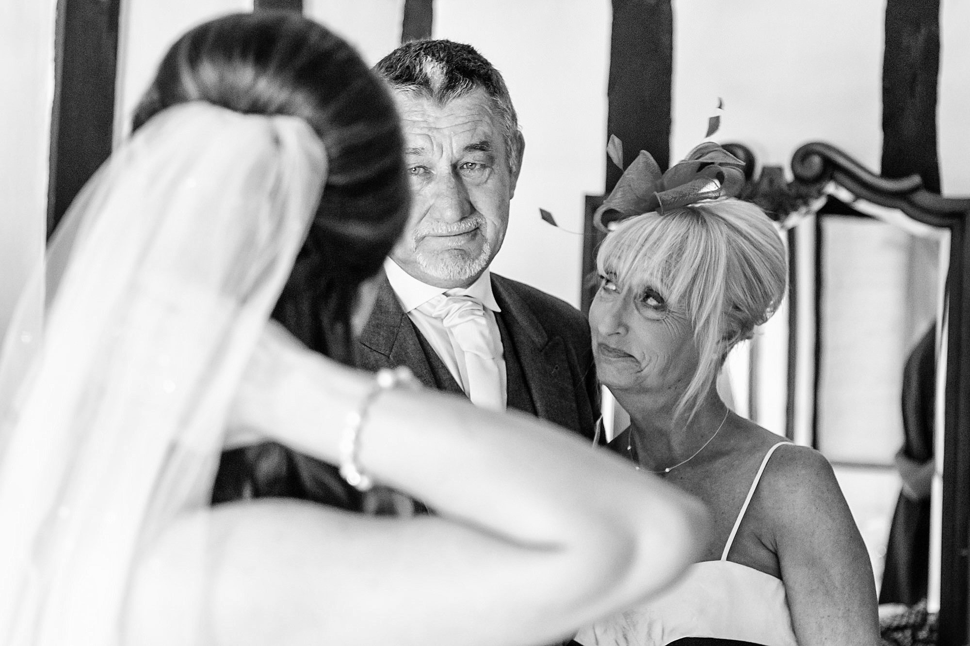 mum and dad look at bride Leez Priory Wedding