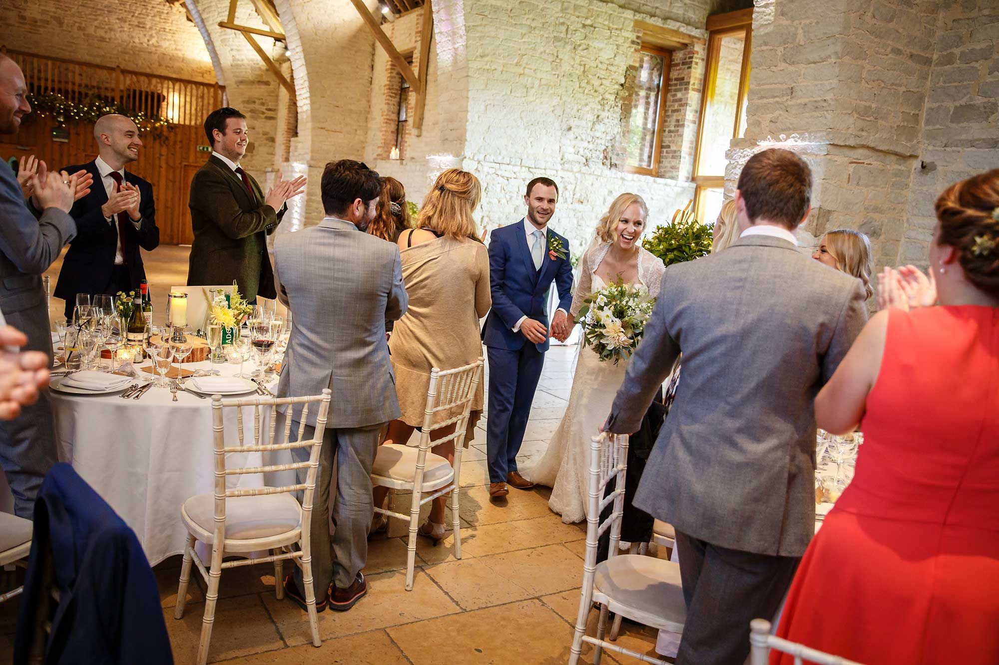 bride and groom enter the tithe barn hampshire