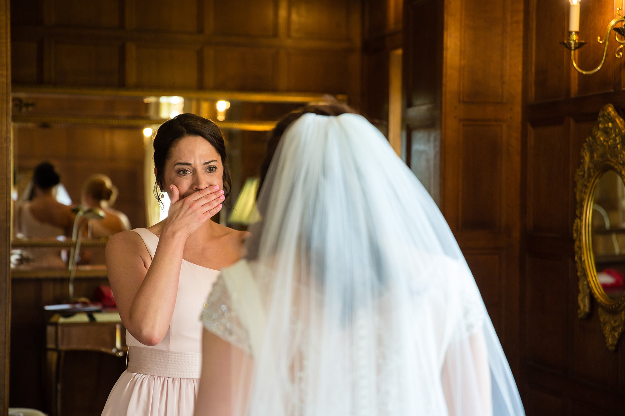 her bridesmaid covers her mouth is shock at how beautiful she looks.