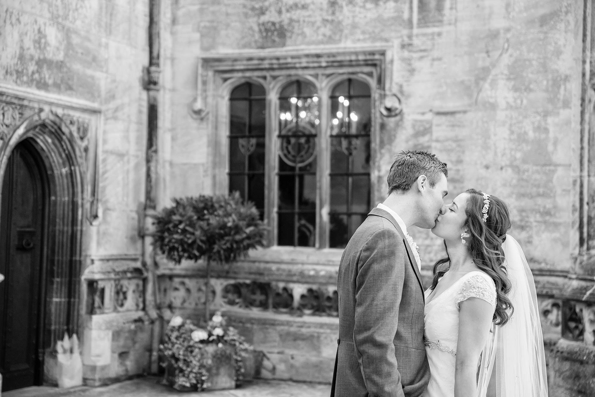 A black and white picture of the couple kissing in the courtyard at Hengrave Hall
