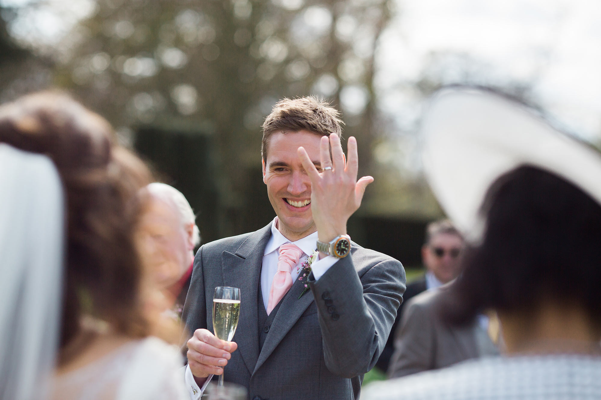 The groom shows off his ring in the west terrace of Hengrave Hall