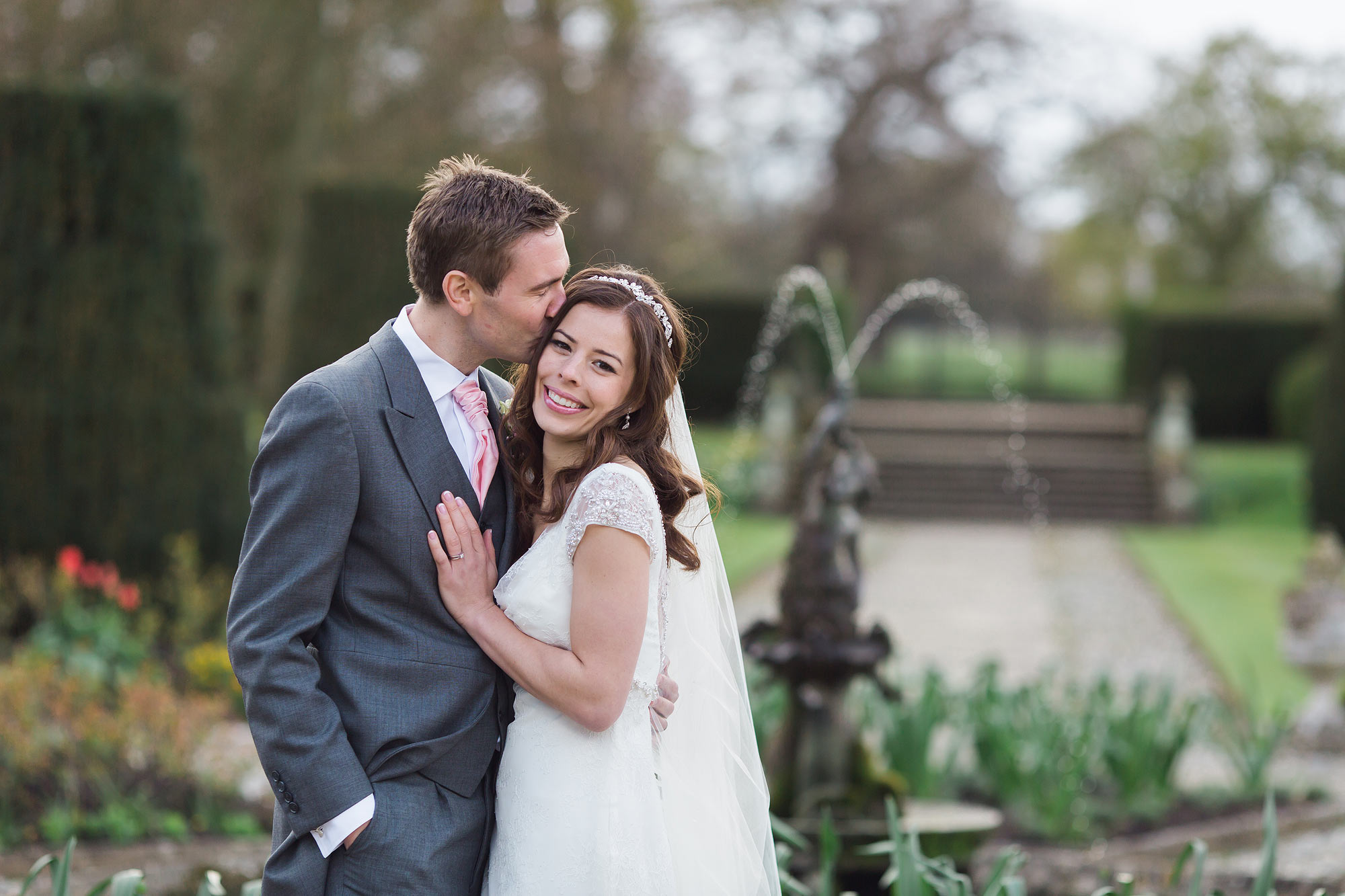 Wedding photography at Hengrave Hall. Jack kisses Amy.