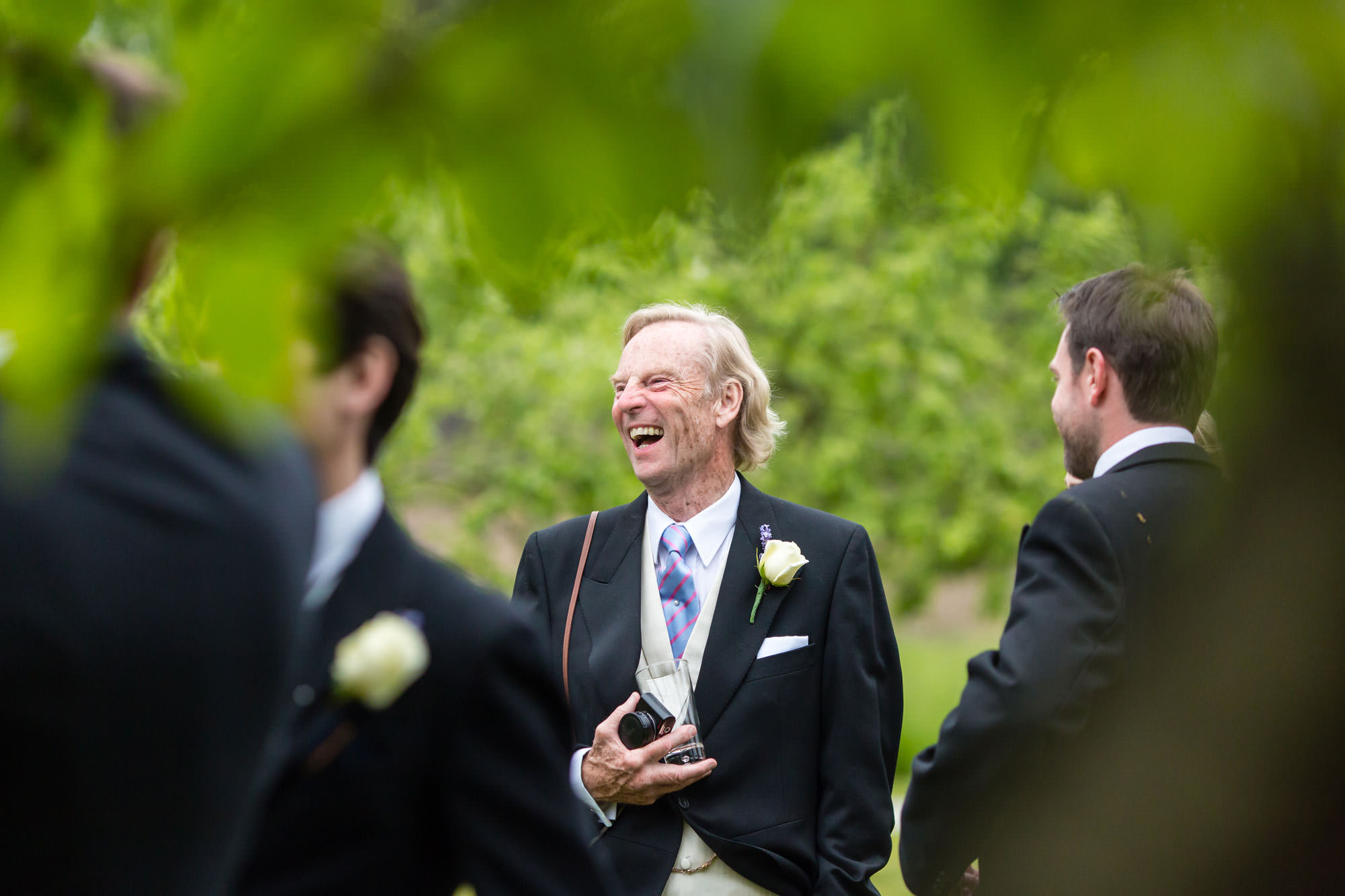 Grooms dad laughs with his friends