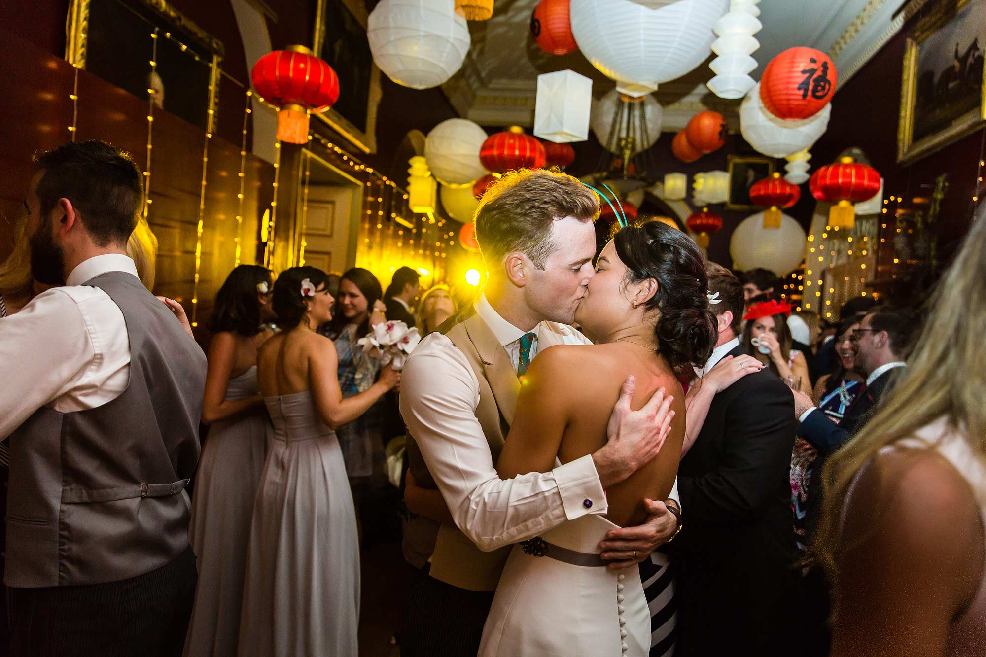 The couple kiss under lanterns