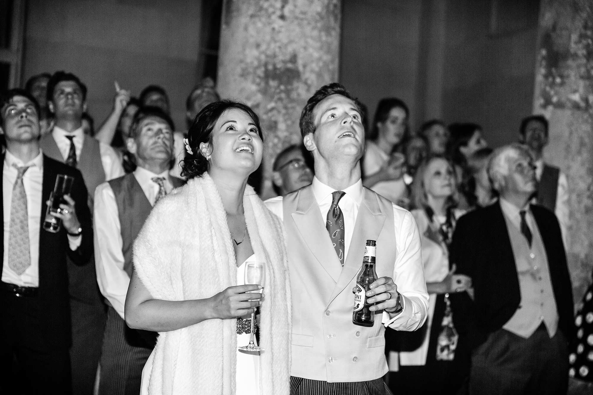 bride and groom look up into the sky to watch the fireworks