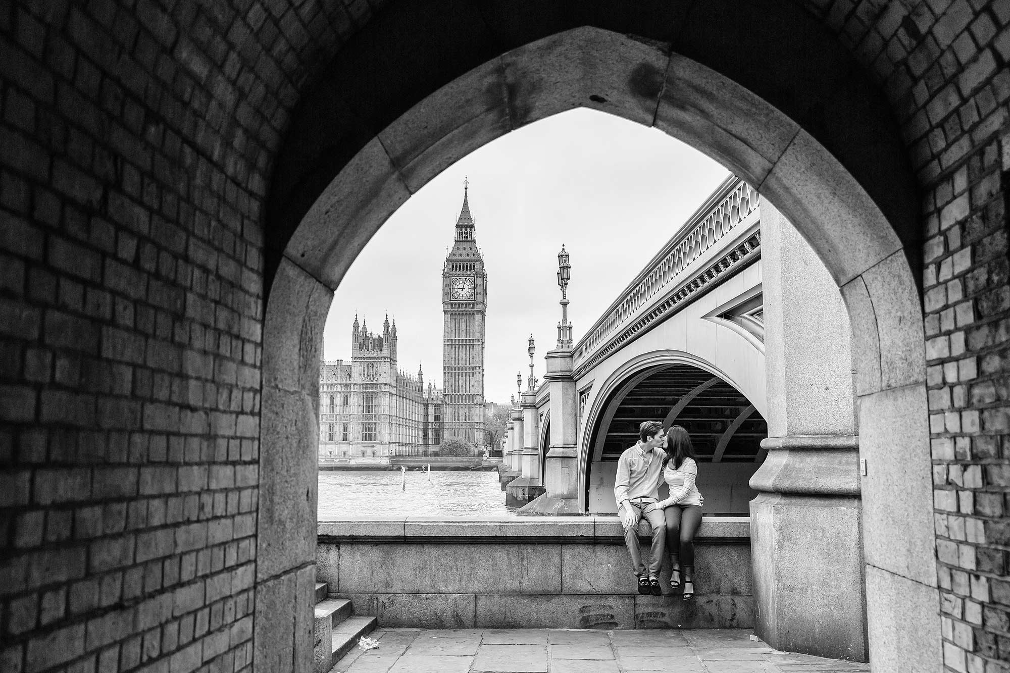 The engaged couple kissed under a bridge, black and white with Big Ben in the background.