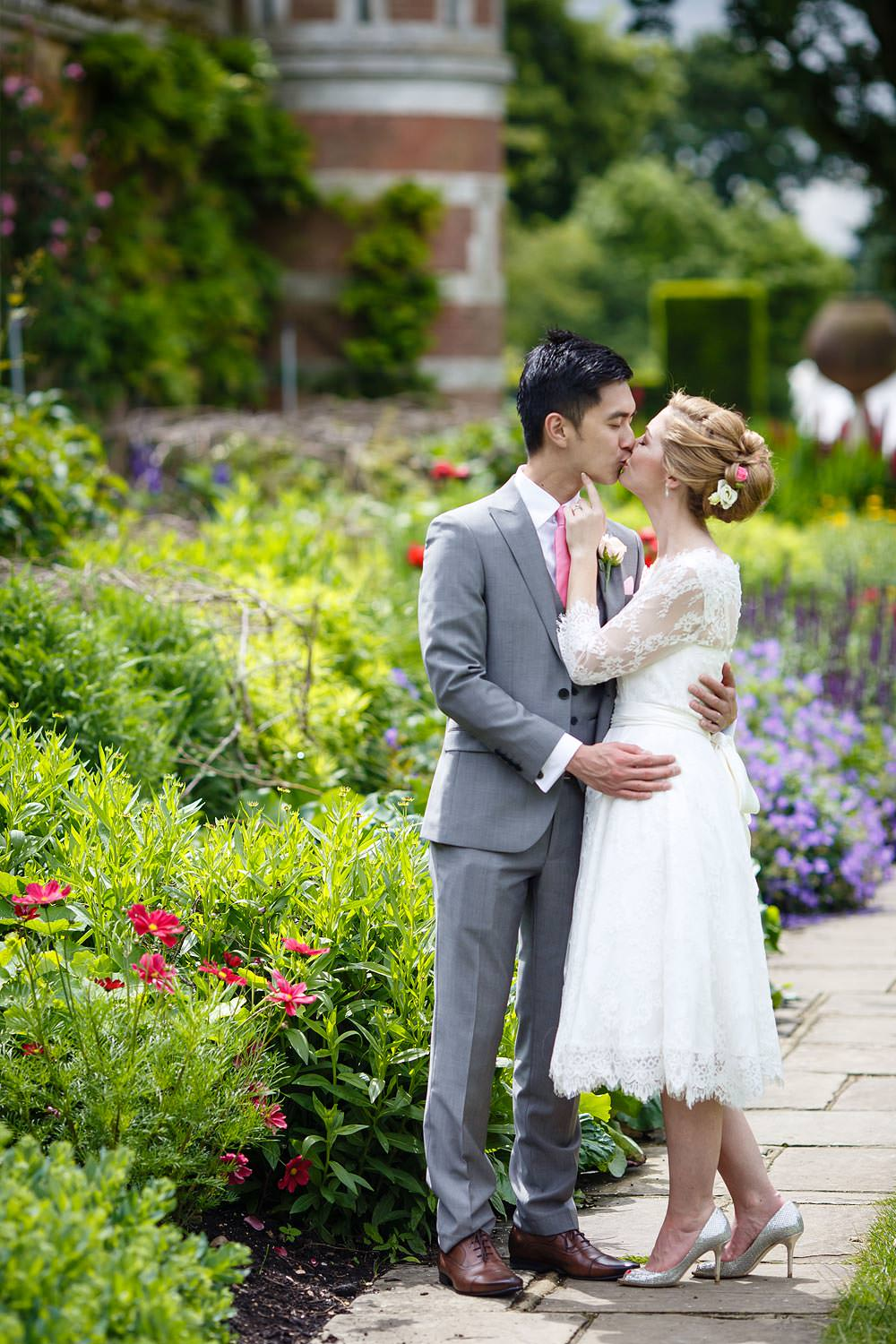 Bride and groom kissing in the gardens of Cliveden House on their wedding day