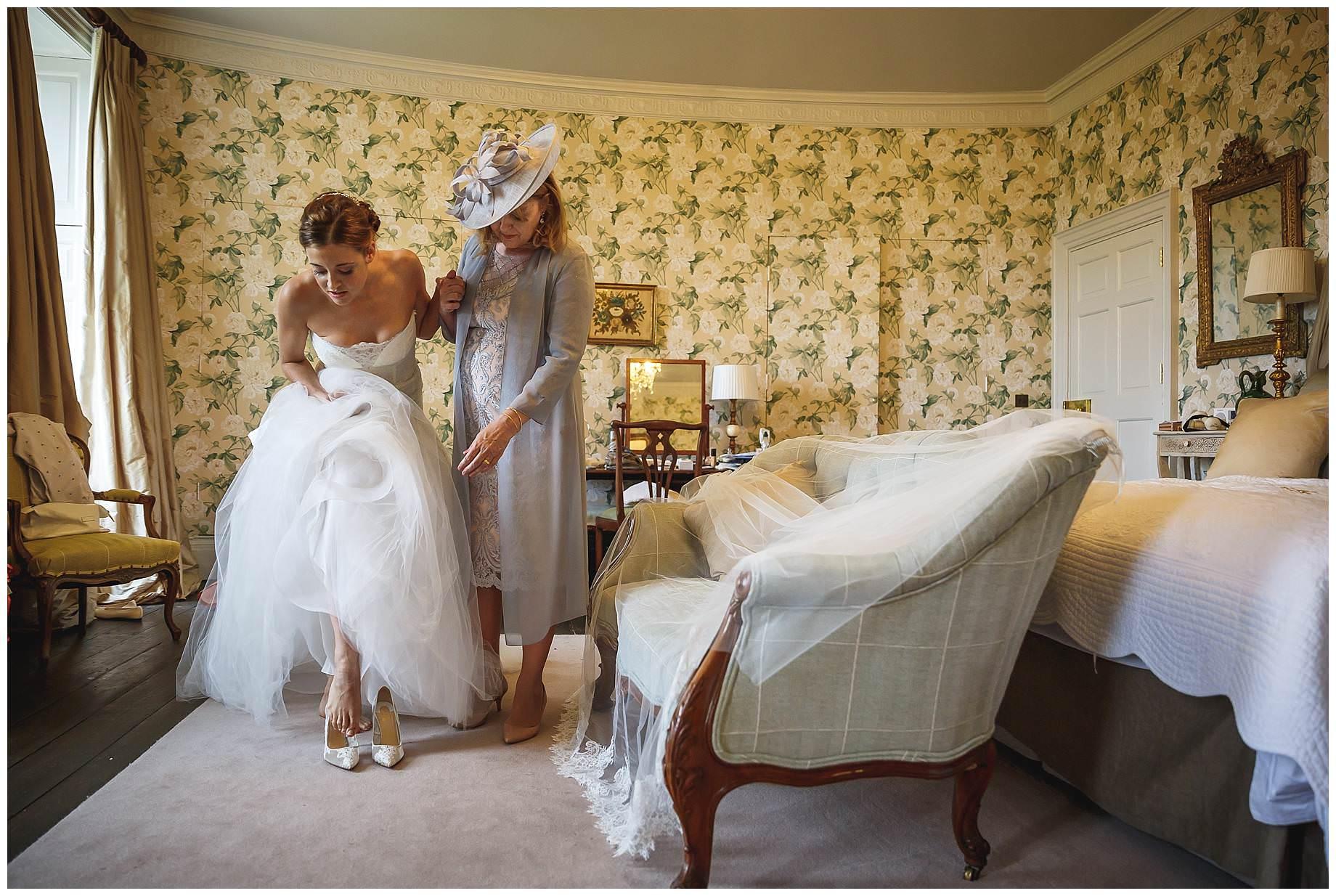 Goodnestone Park Wedding Bride putting on shoes
