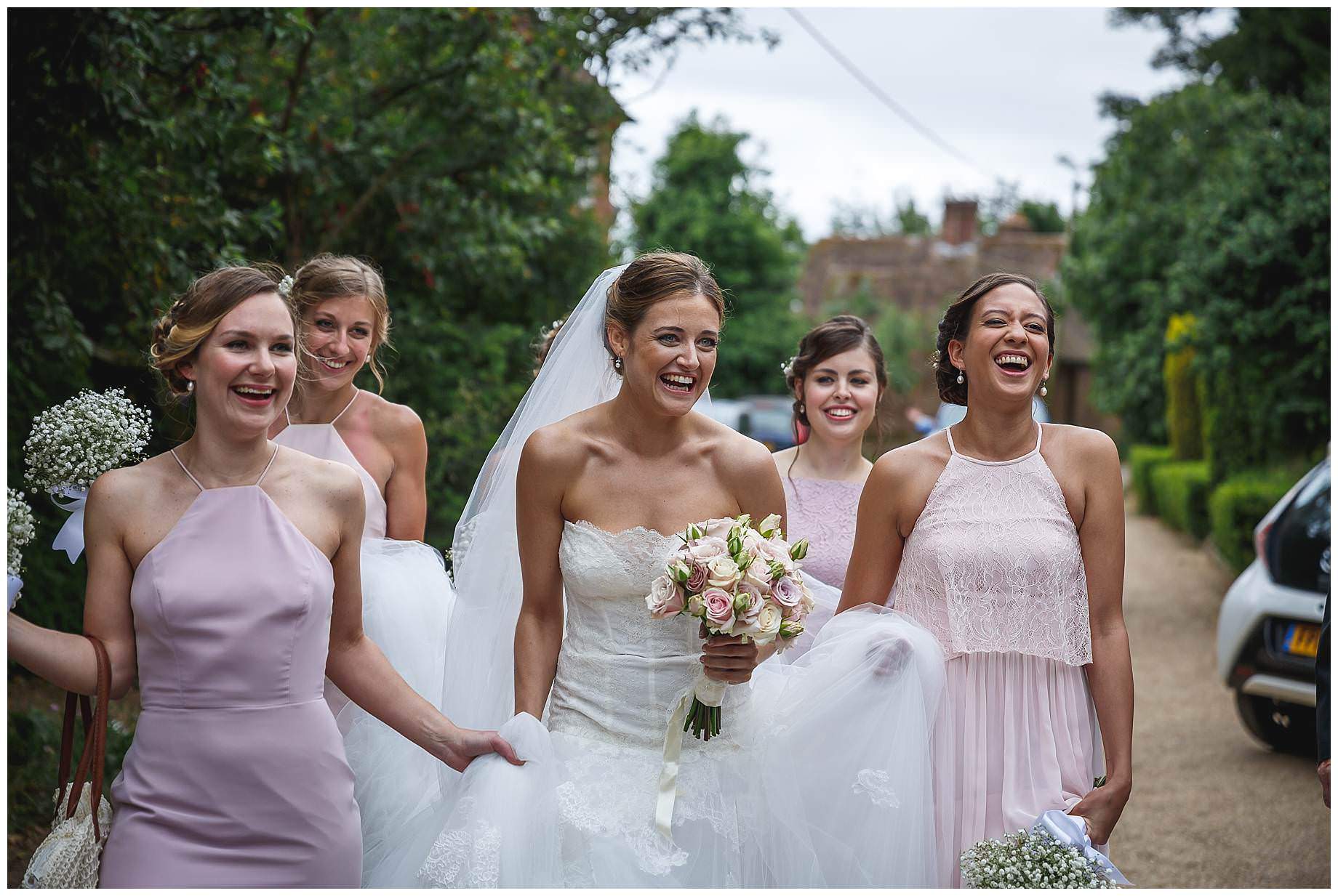 bride laughing with her bridesmaids on the way to the church
