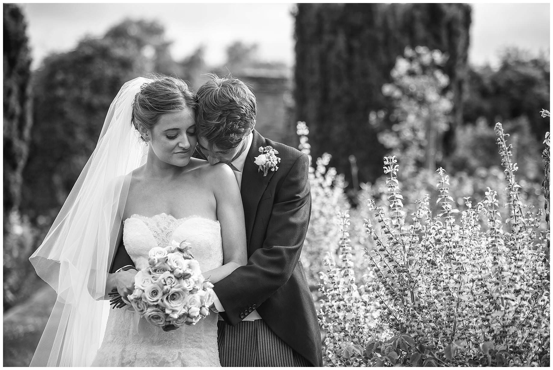 black and white shot of the bride and groom surrounded by flowers. The groom kissing the brides shoulder.