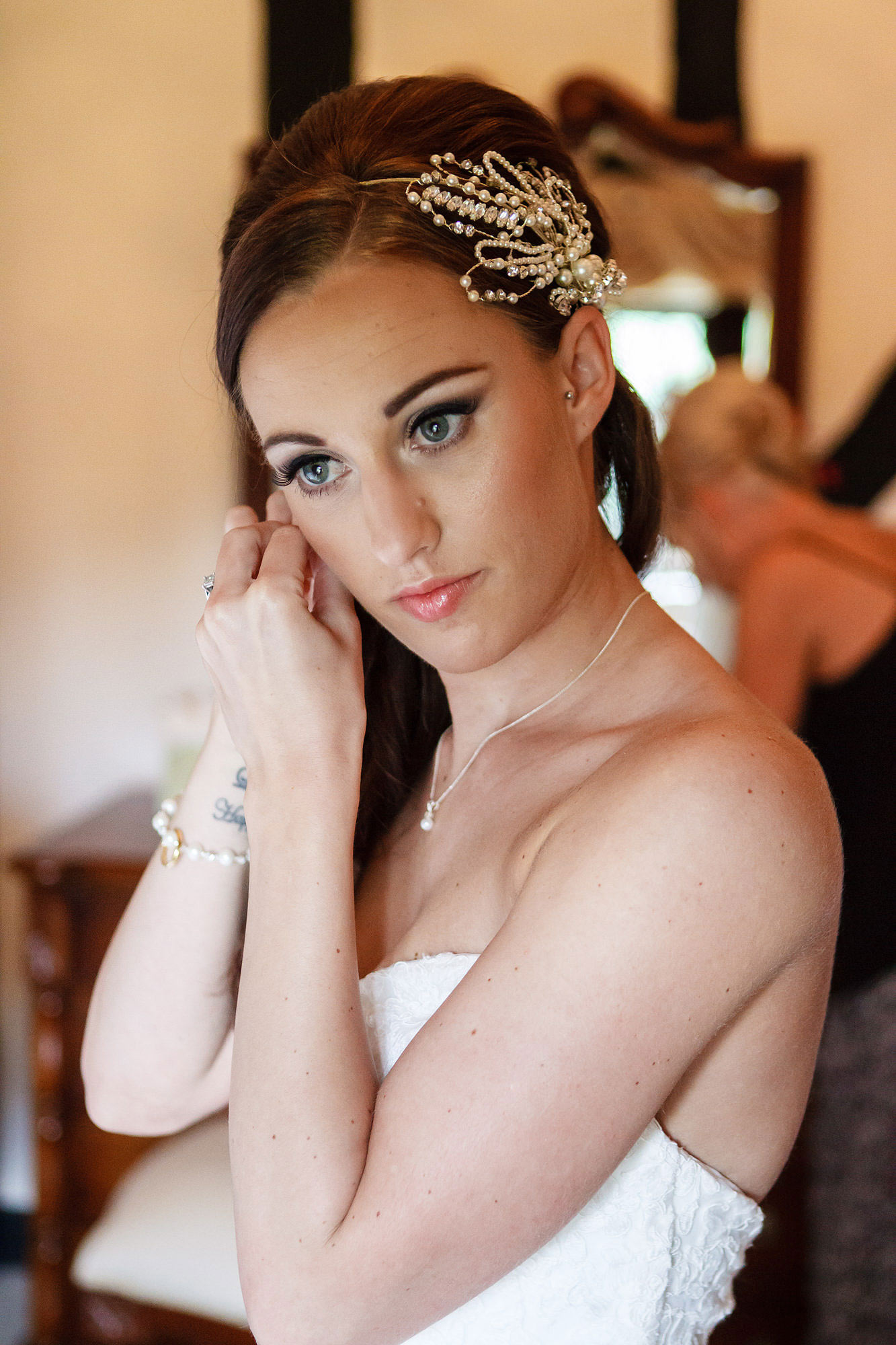pretty bride putting on earrings at Leez Priory