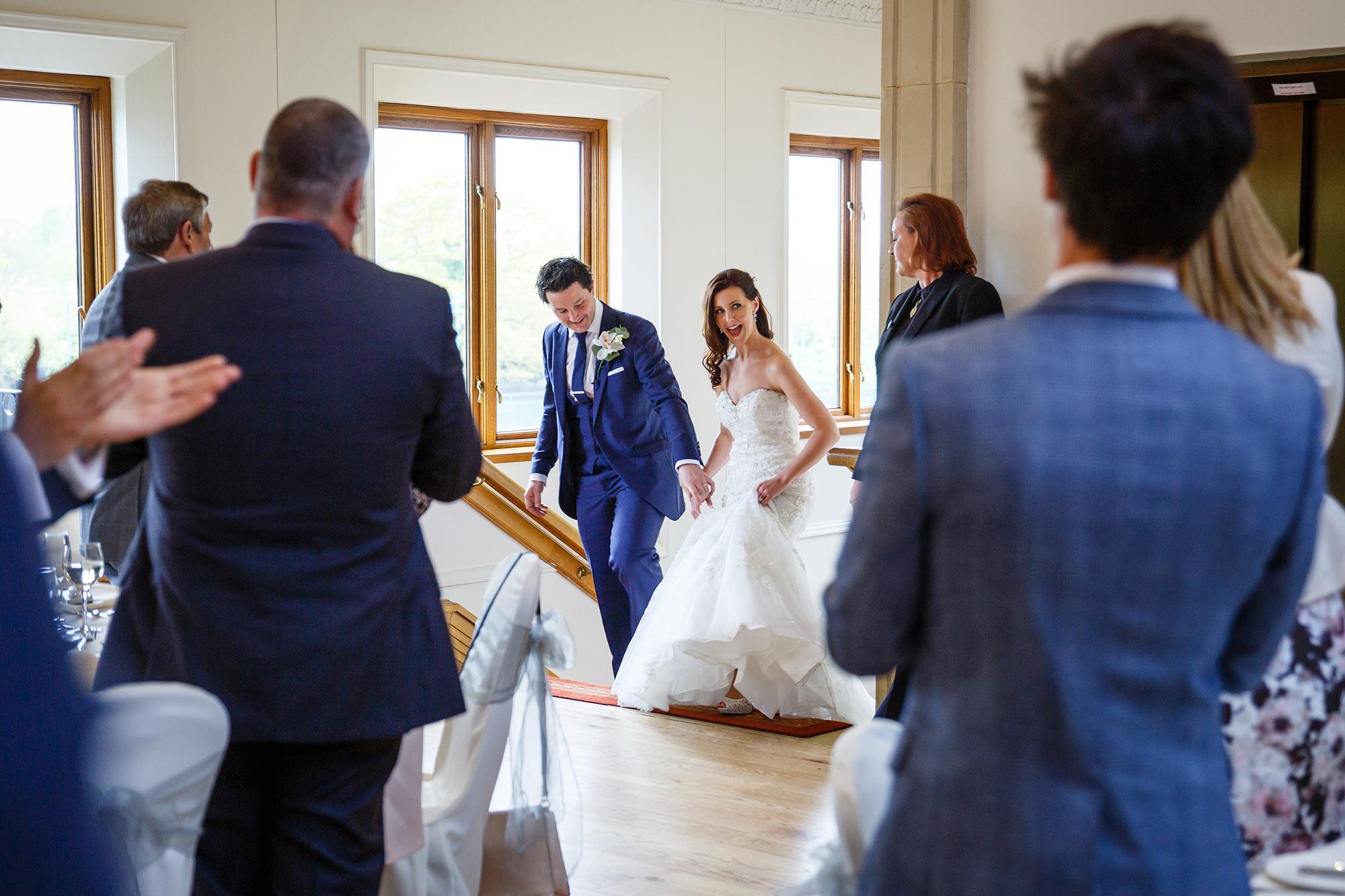 bride and groom enter stockbrook manor wedding breakfast