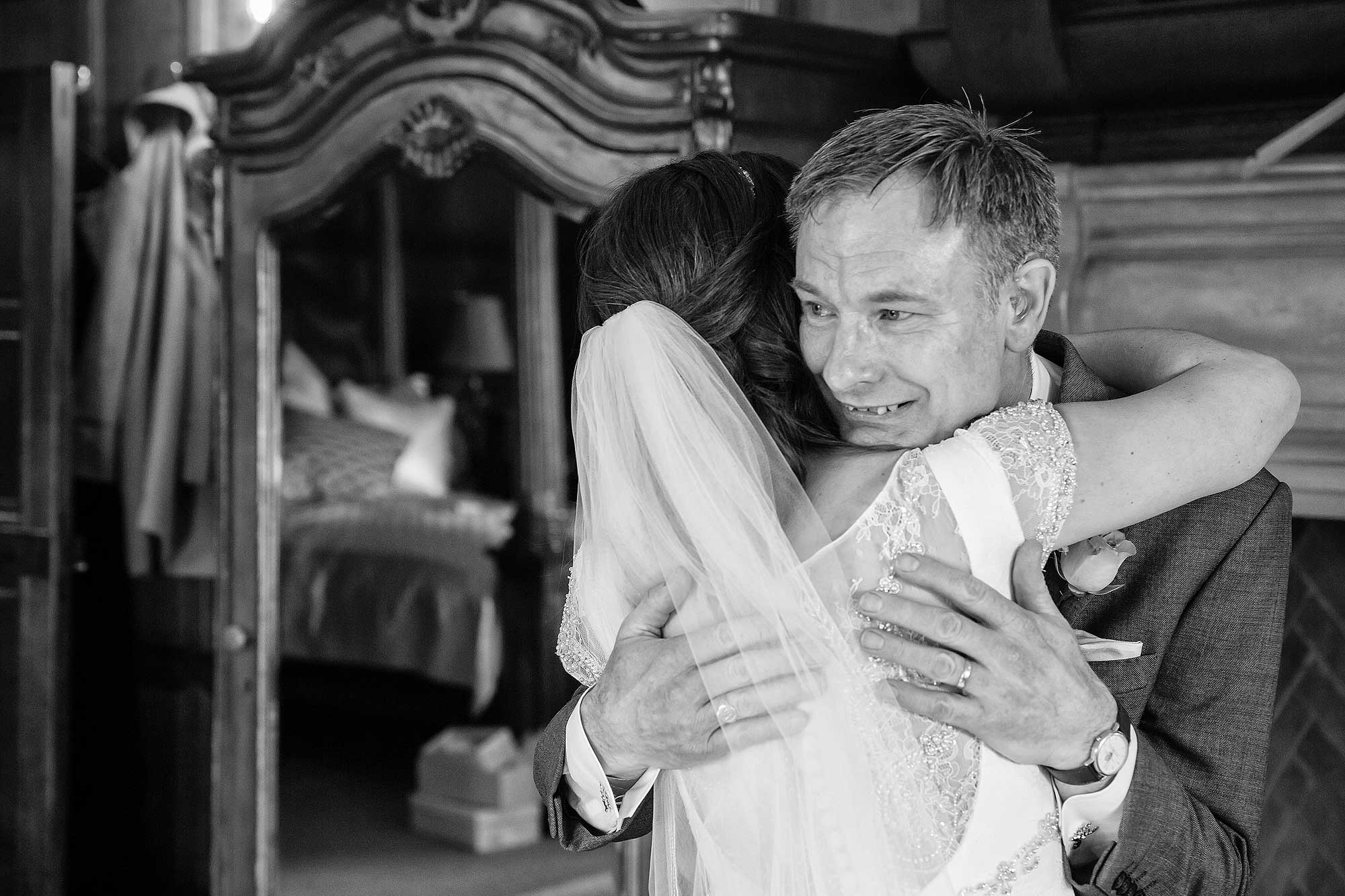 Amy's dad see's her for the first time in her wedding dress and hugs her.