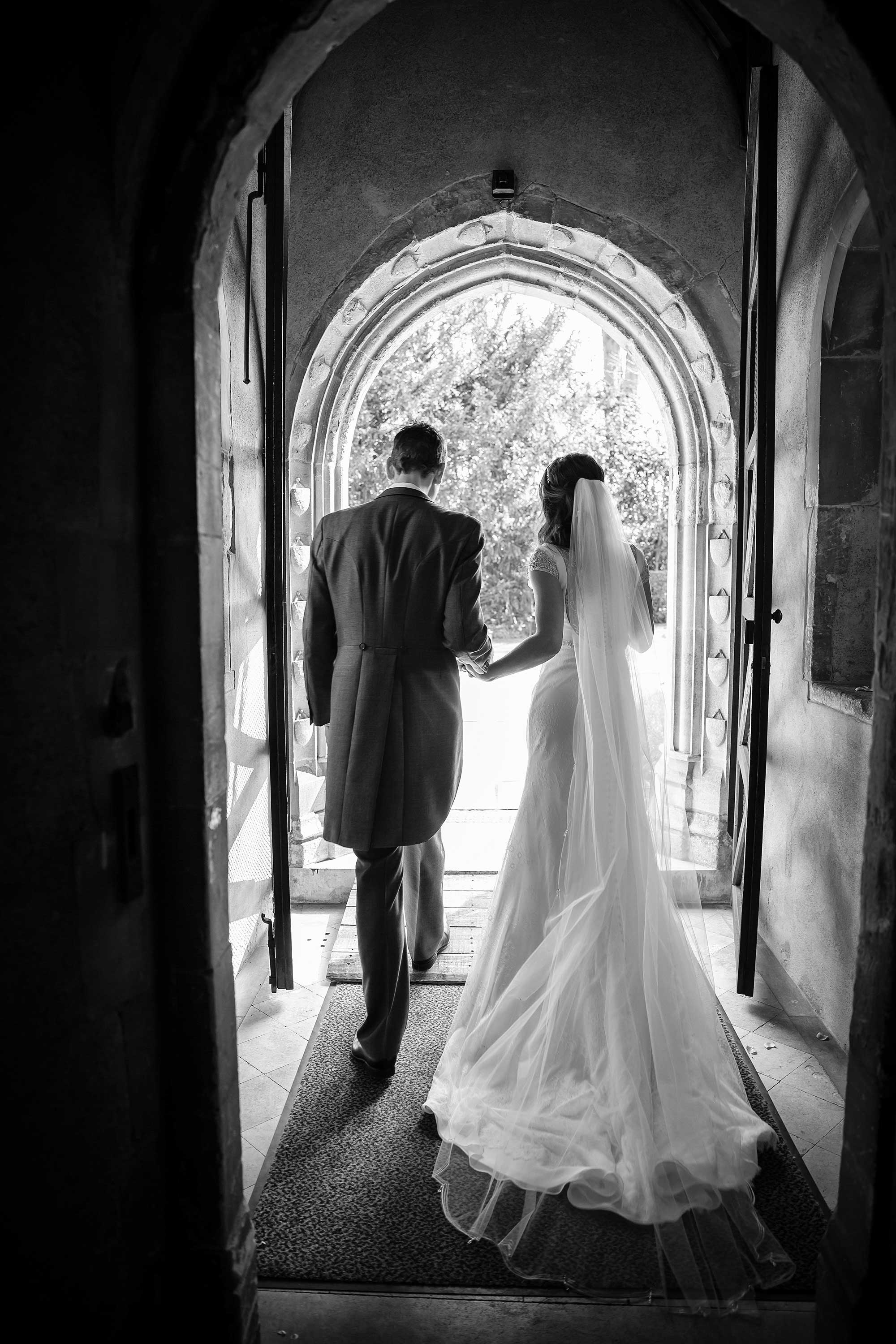 Black and white image of the couple exiting the church taken from behind them, so you can see the back of the brides dress.