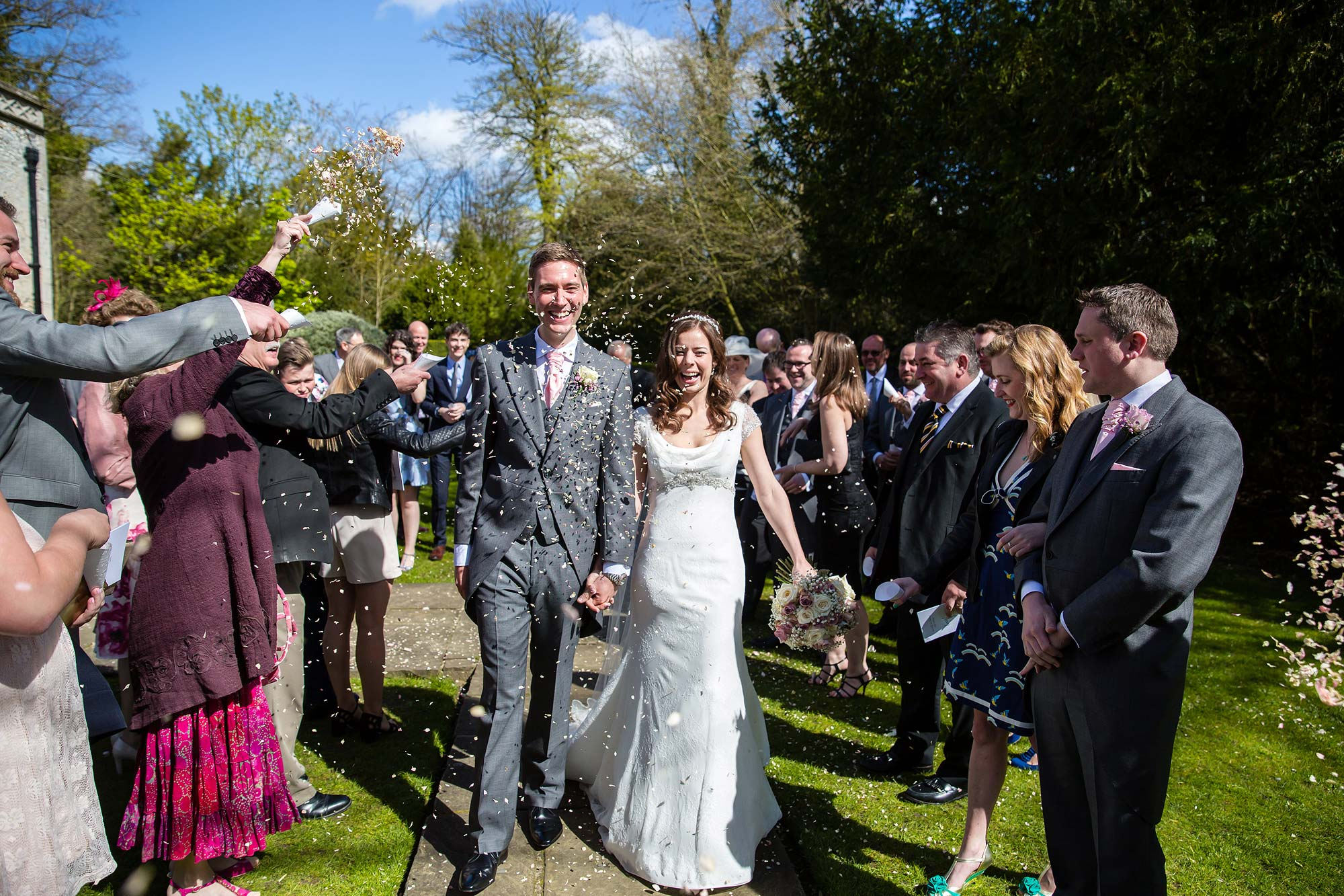 The bride and groom are showered in confetti outside Hengrave Hall church