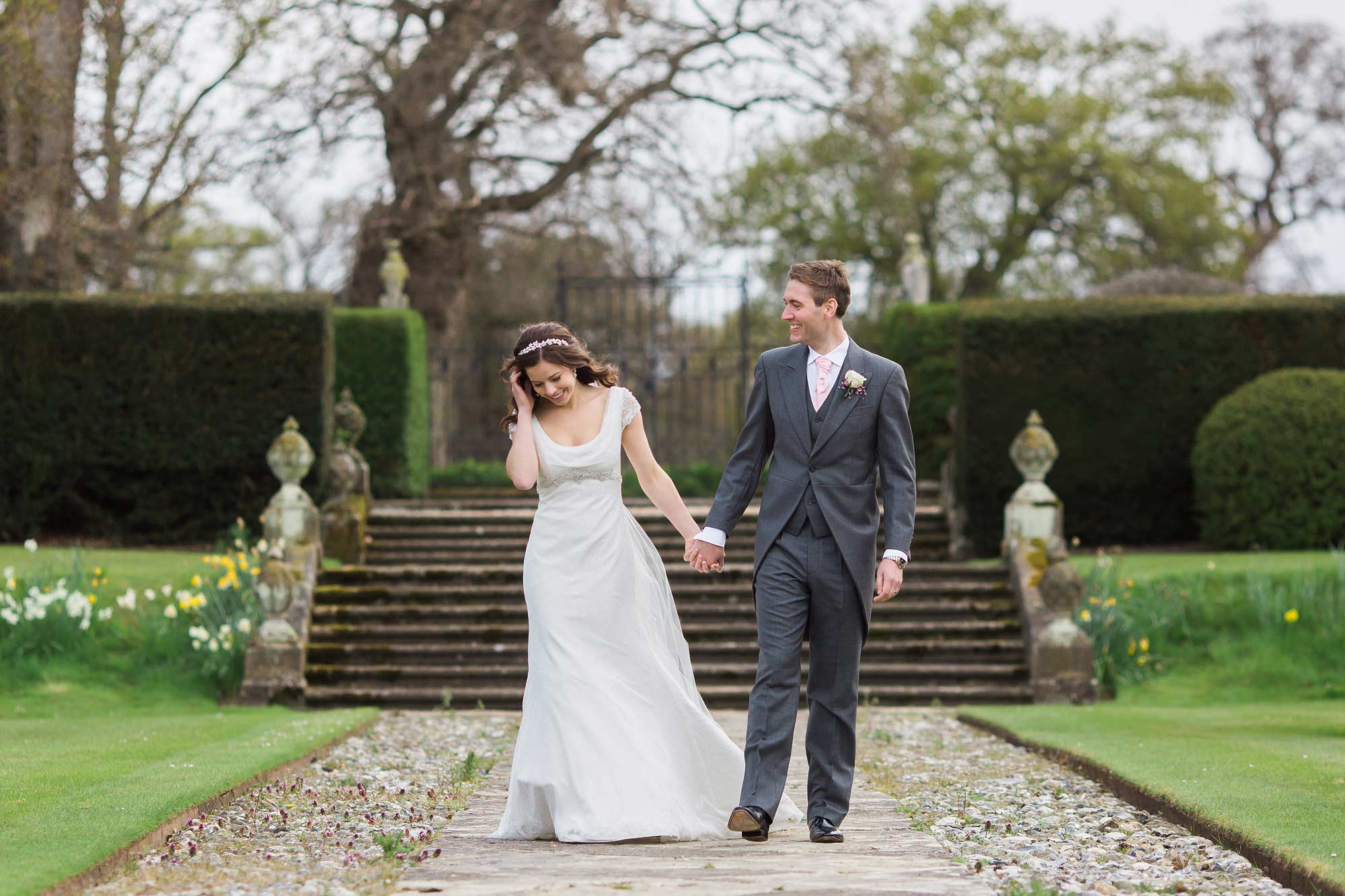 Jack and Amy walk hand in hand for their Hengrave Hall Wedding Photographer