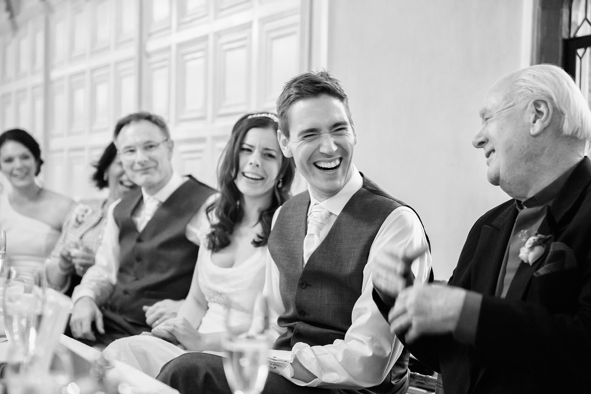 The groom laughs at his best man's speech