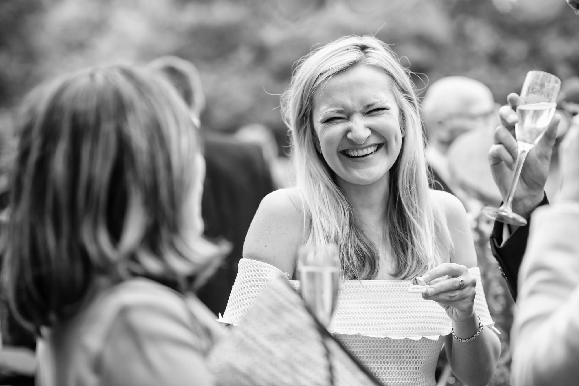 lady laughing at friend in black and white