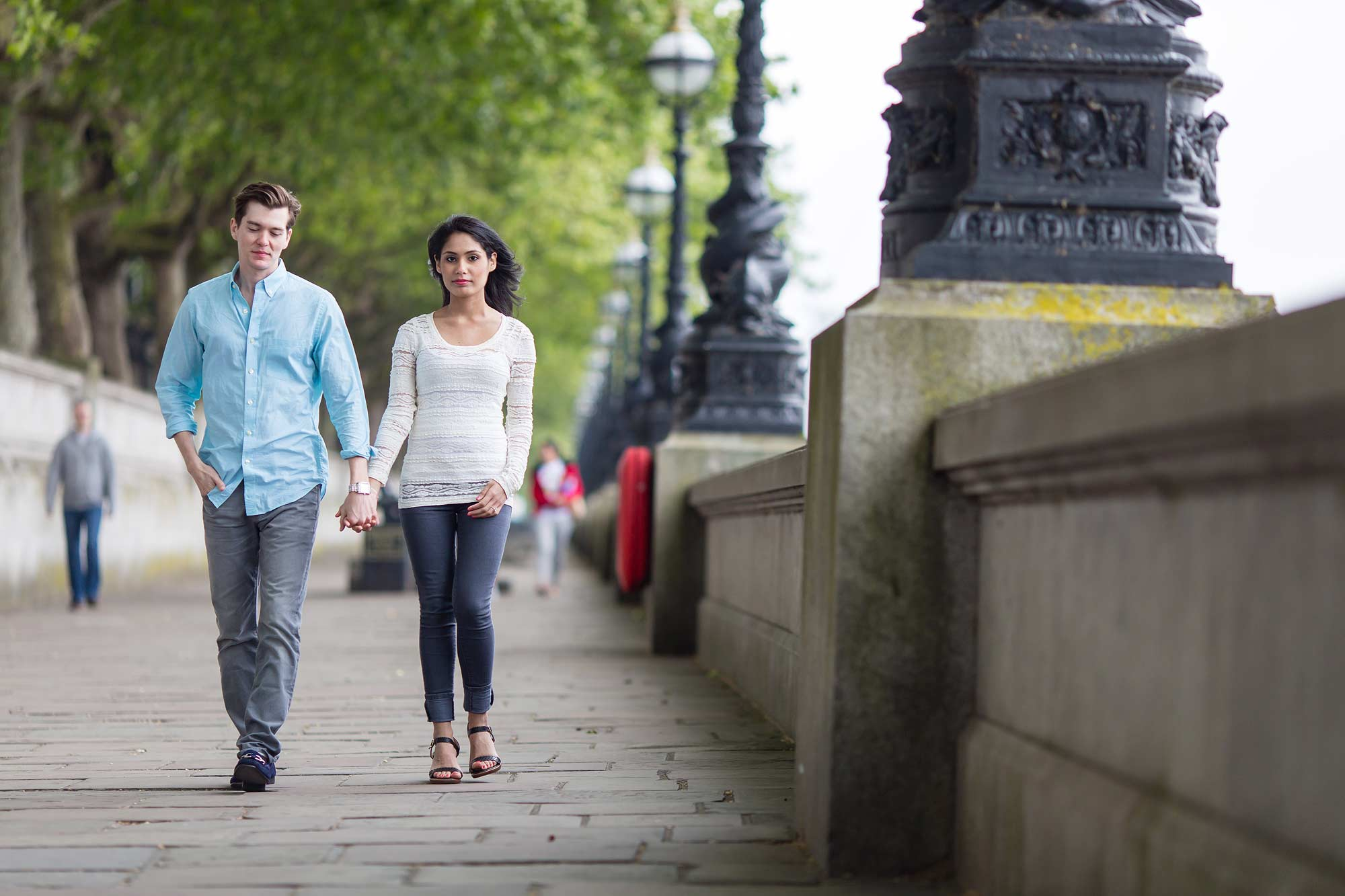 The hold hands and walk towards the camera on embankment