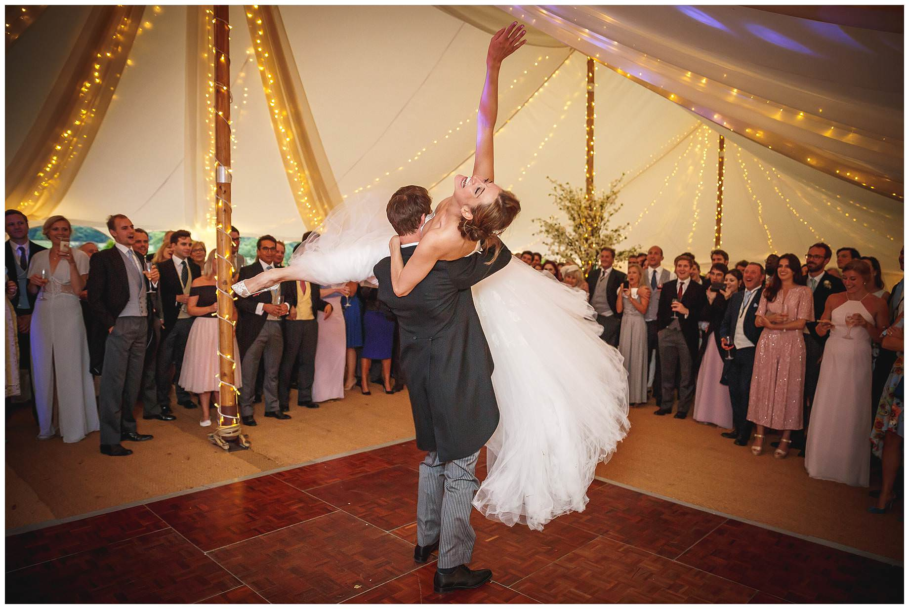 bride is lifted up by groom