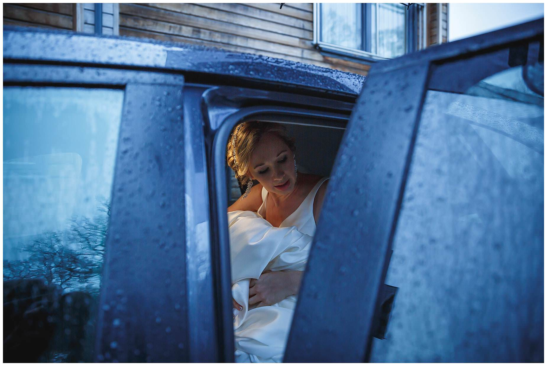 Raining wedding at Northbrook Park Bride in wet car
