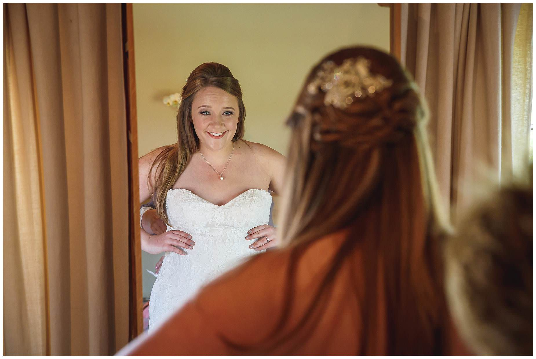 Bride getting dressed at Bury Court Barn Wedding
