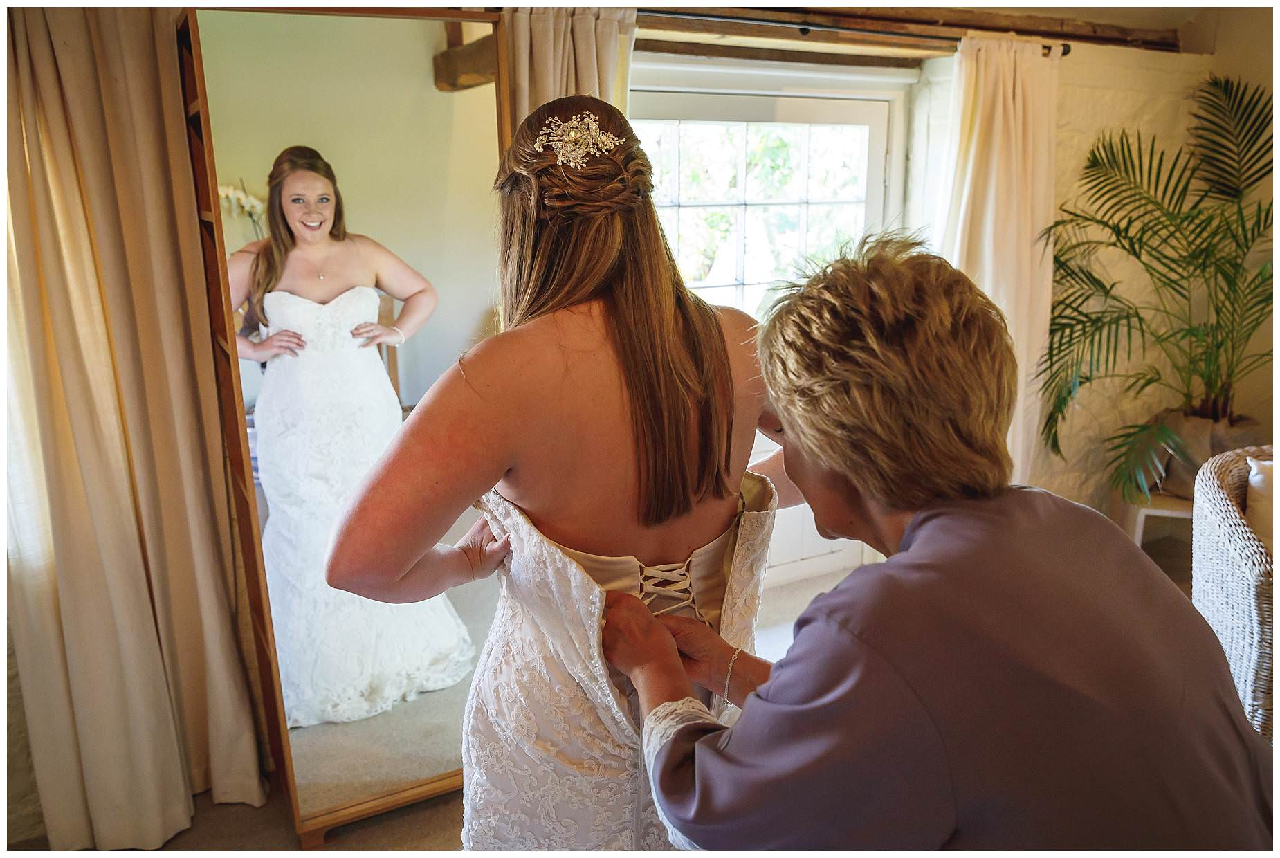 Mum helping with brides dress