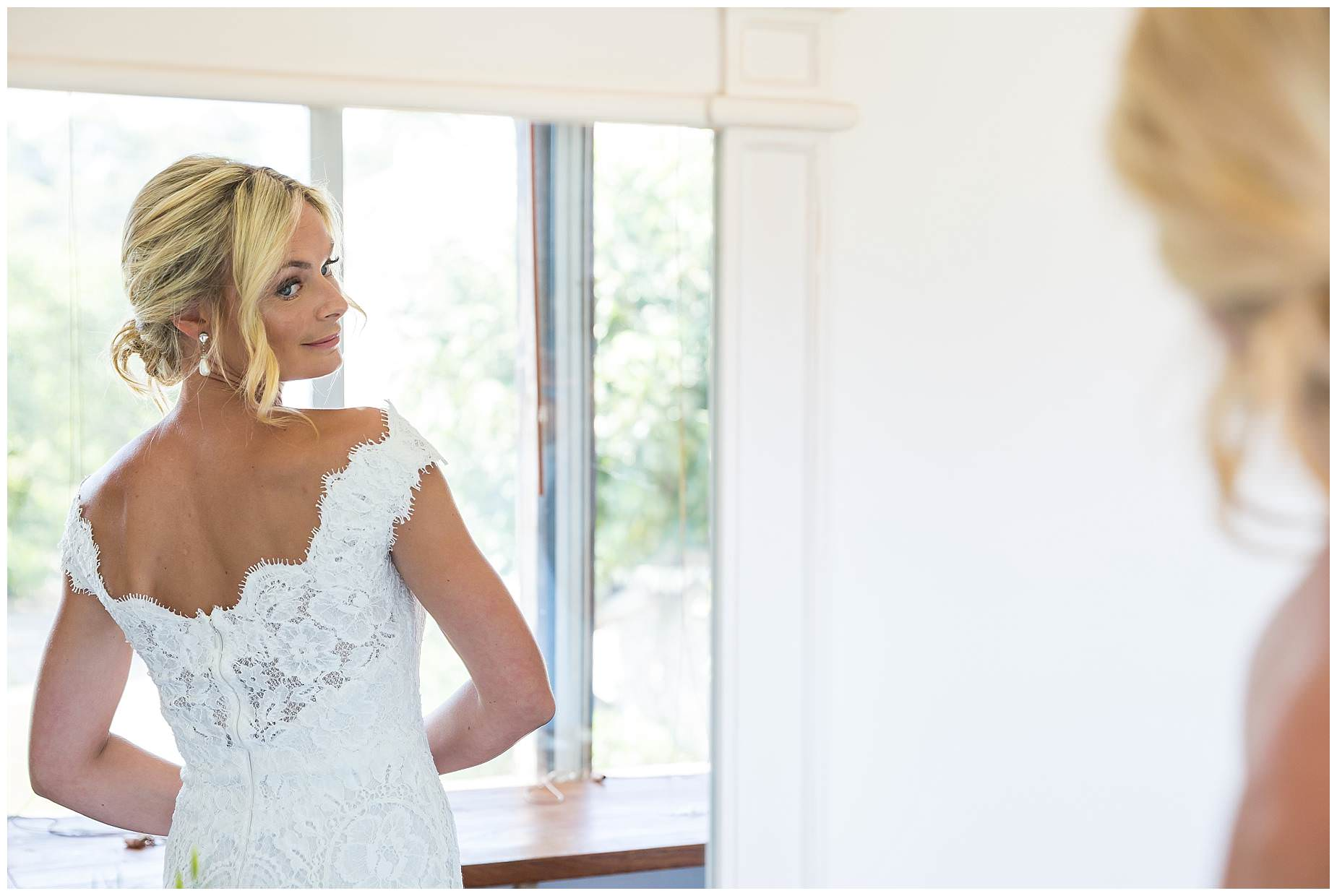 bride looking at the back of her dress in a mirror