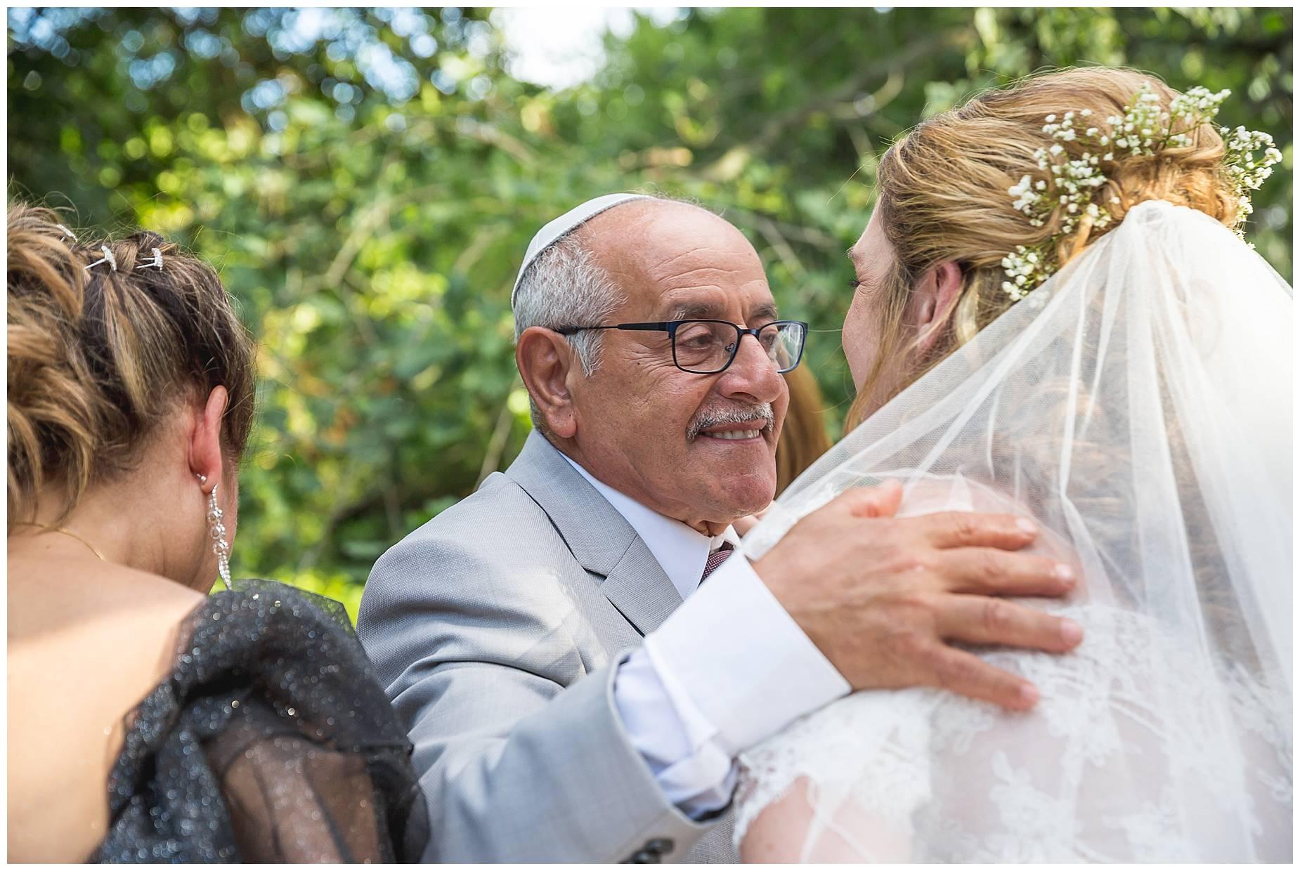 grooms dad hugs bride