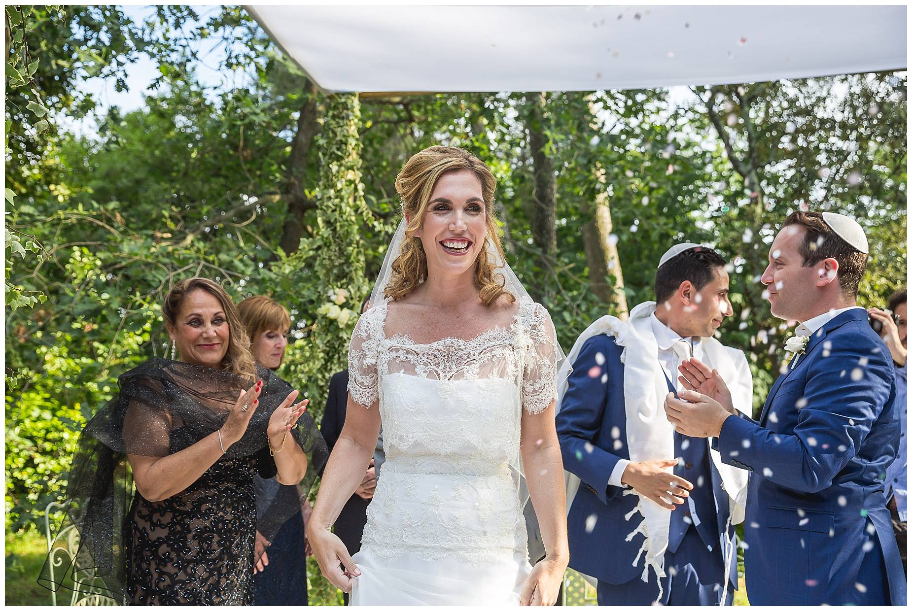 bride smiles through confetti
