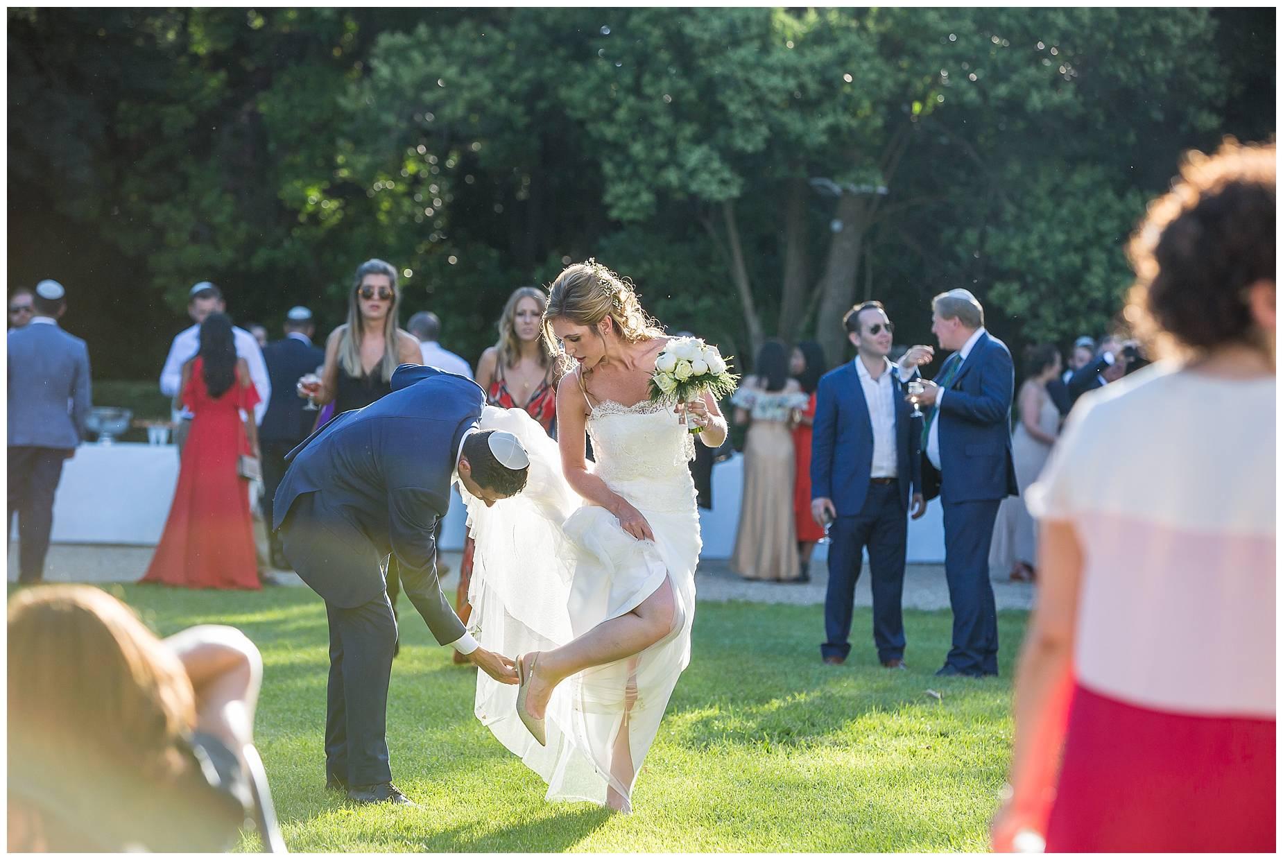 grom picks something off of brides shoe