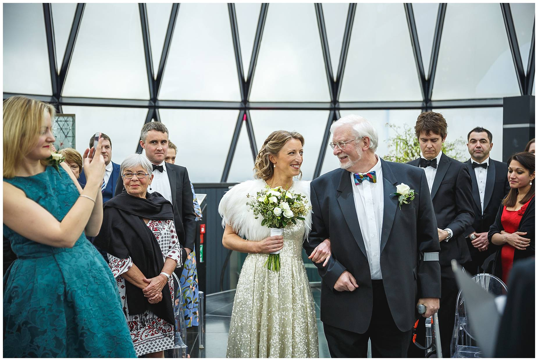 bride walks down the aisle on the arm of her Dad at The Gherkin