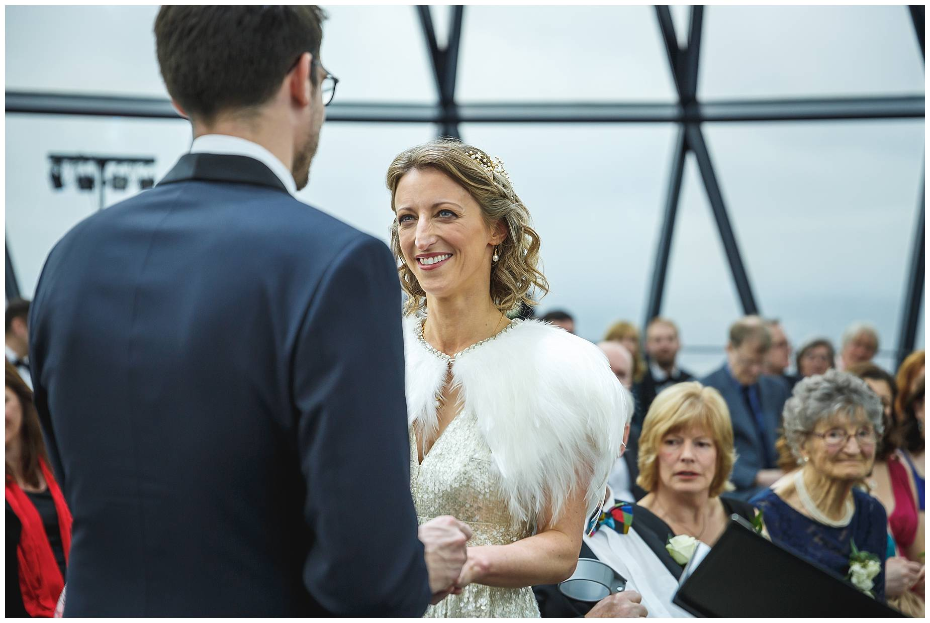 bride looks at groom during their wedding at the gherkin