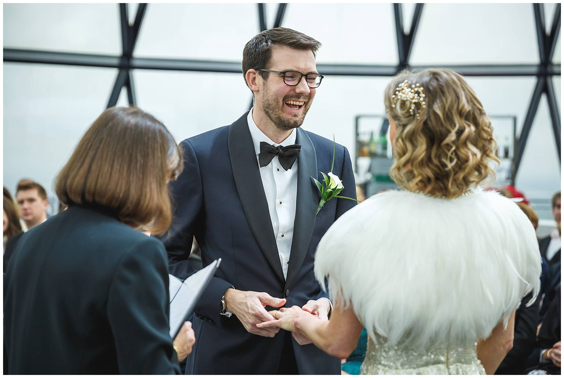 groom smiles at bride during vows