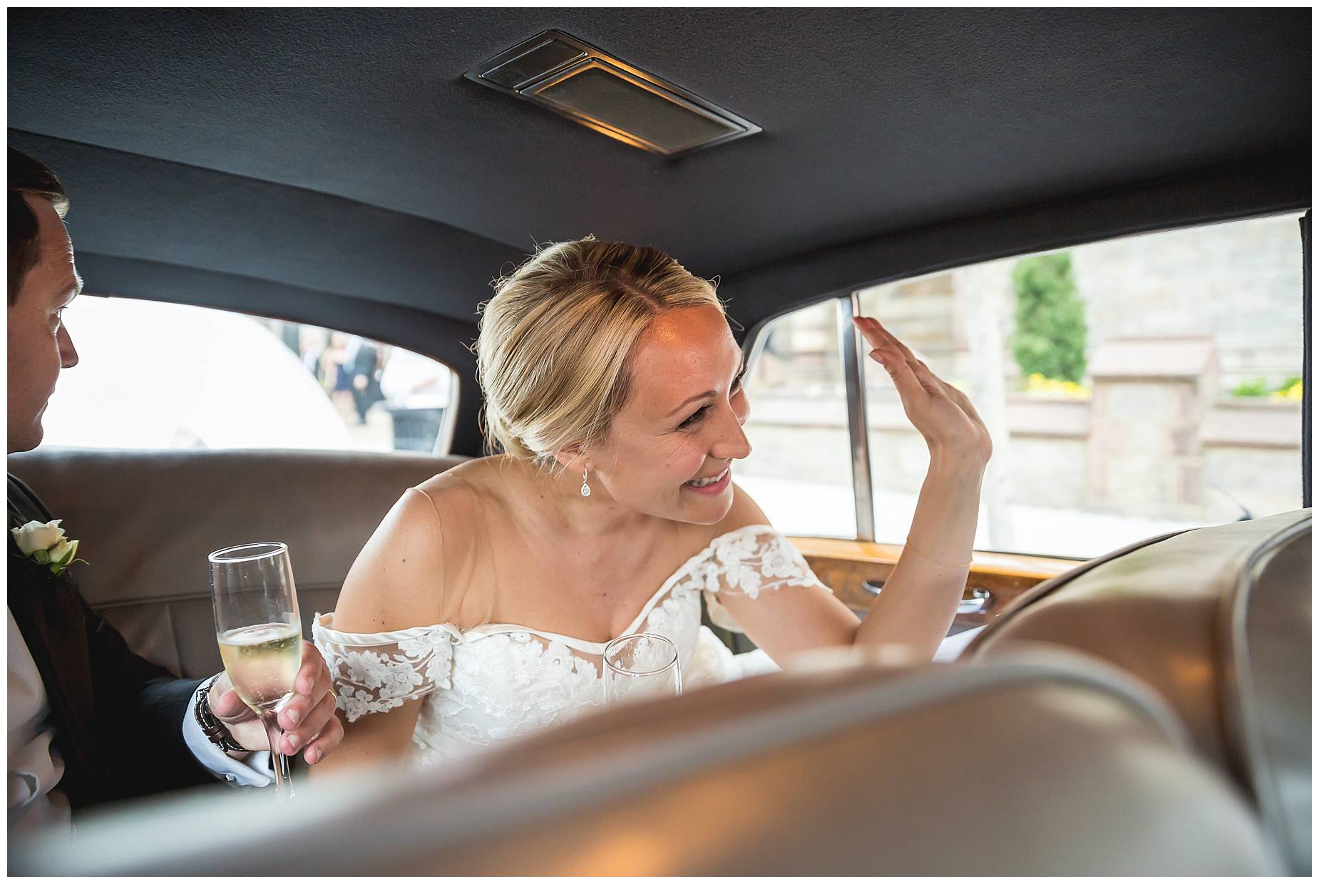 bride waves from her rolls royce