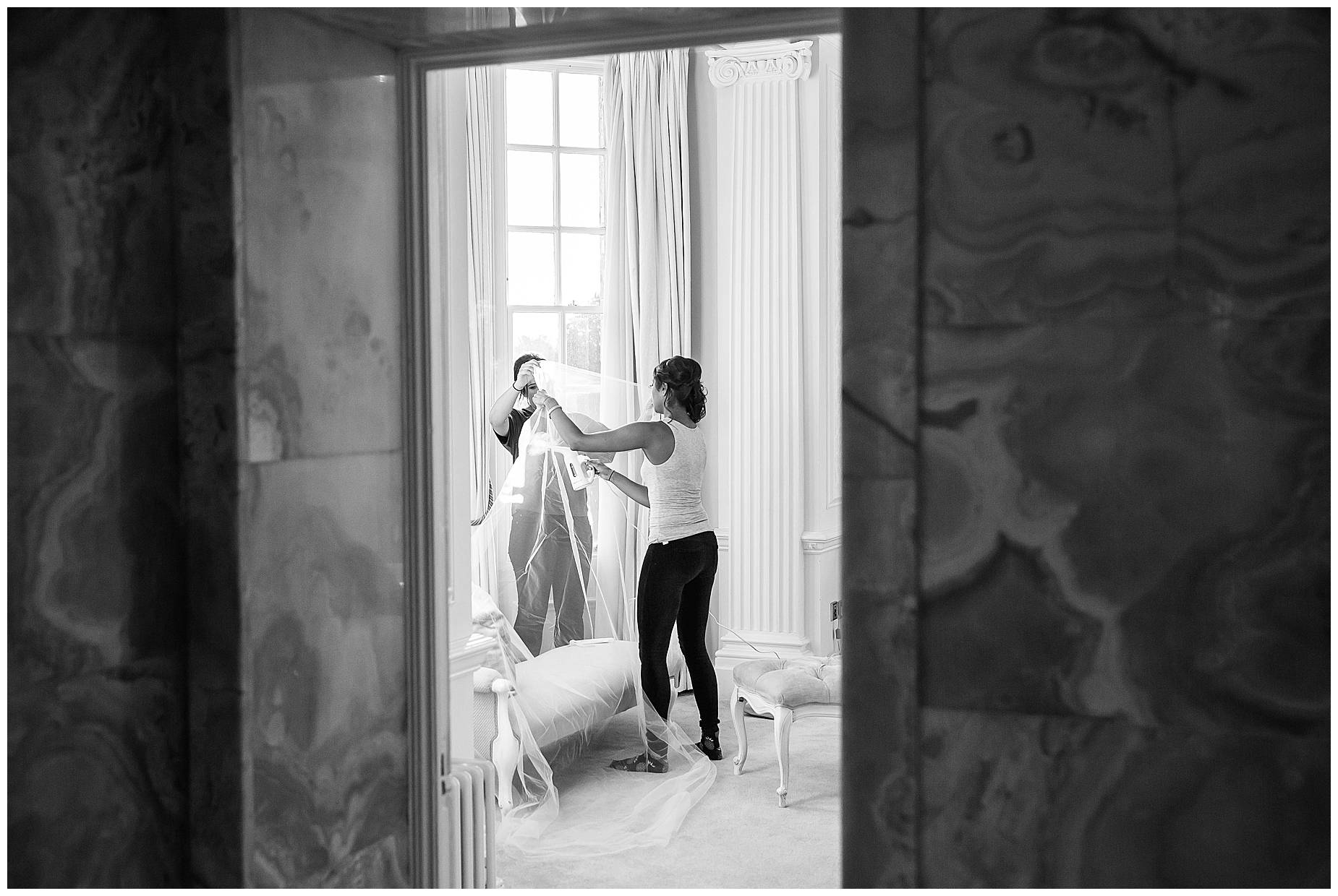 Bridesmaids steaming the dress at Hedsor House Winter Wedding