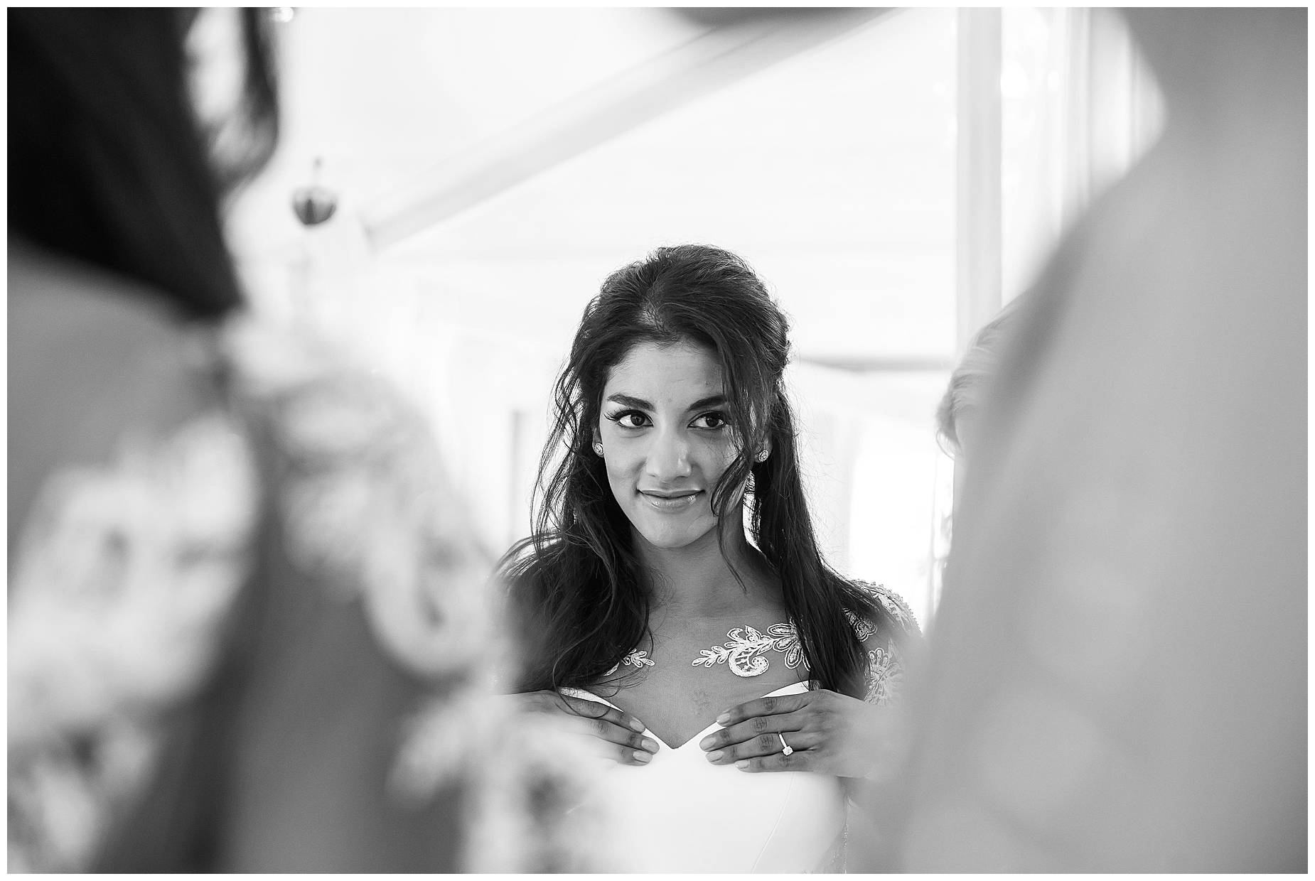 black and white picture of bride looking in the mirror