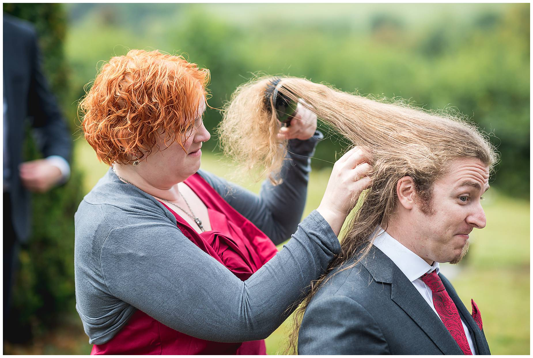 man with long hair gets his hair brushed