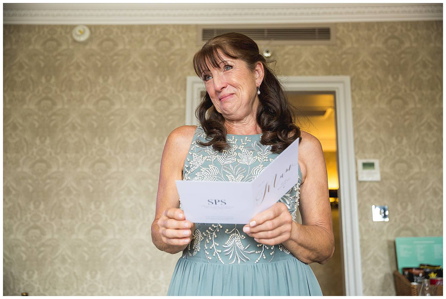 mother of the bride crying over a card