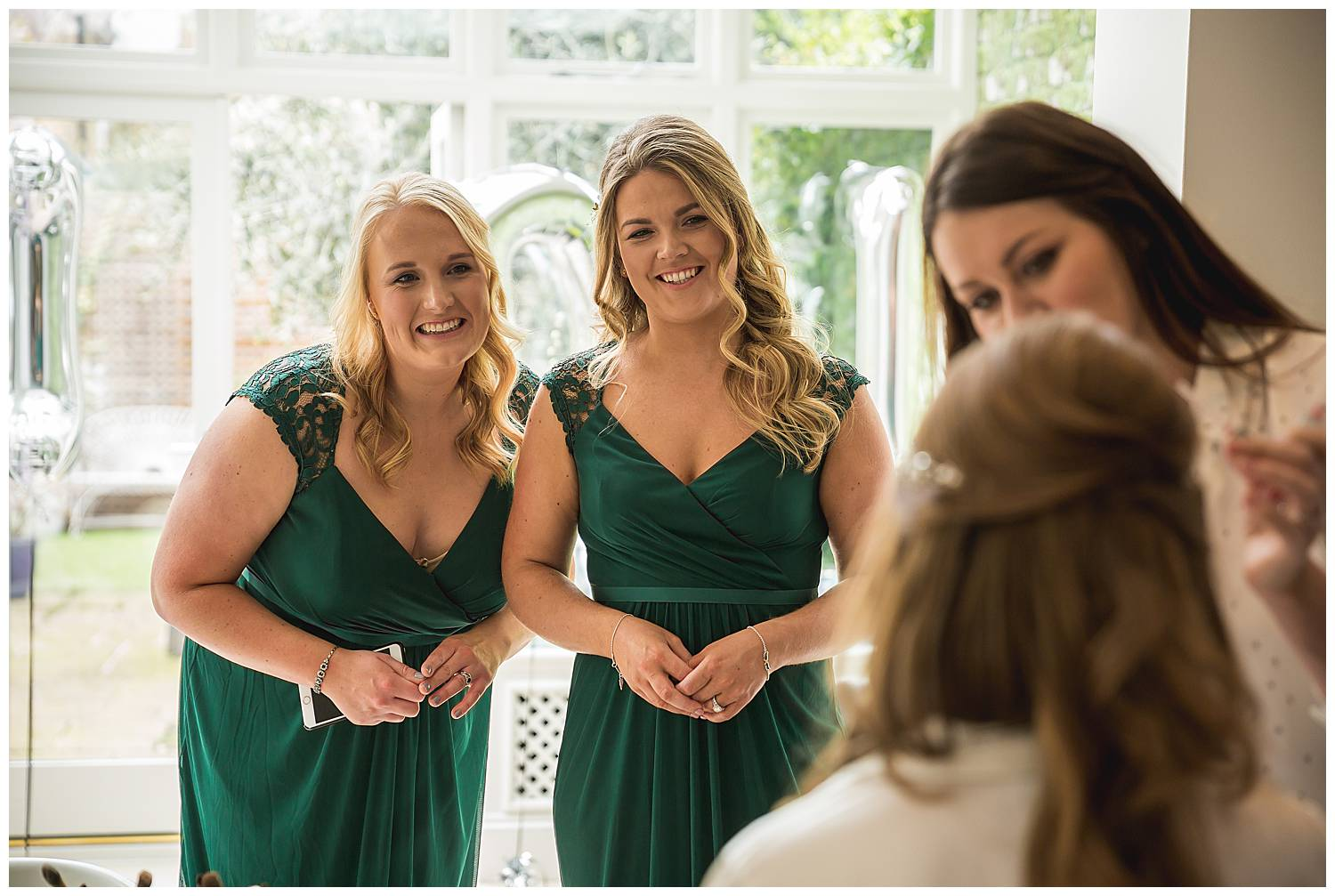 bridesmaids in green dresses are looking at the bride