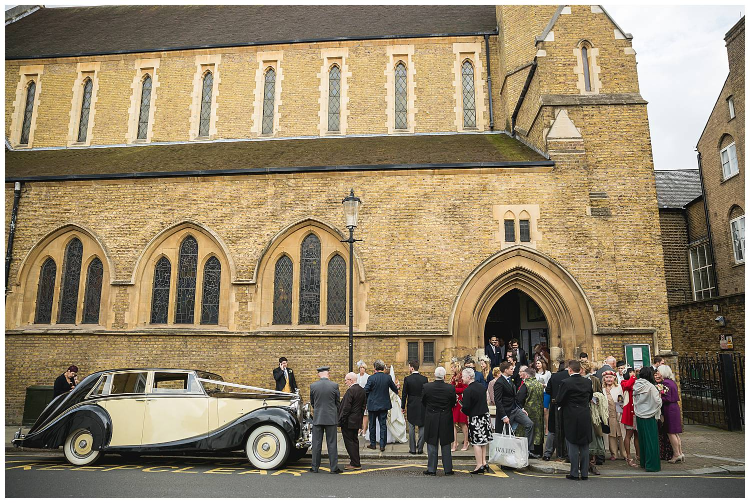 Guests gather outside wedding at St Mary's Cadogan Street SW3