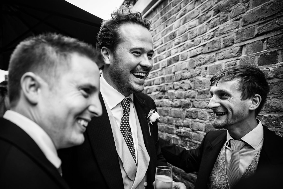 groom smiles with guests