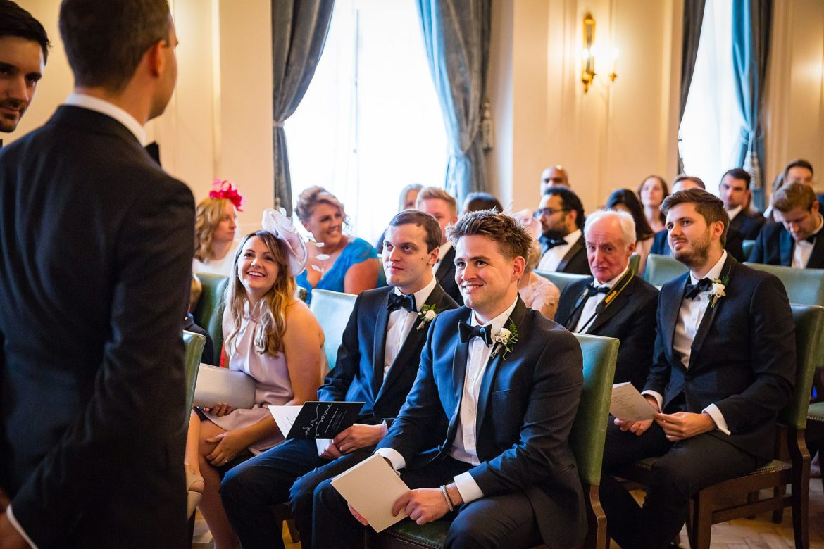 groomsmen smile at groom while he waits for his bride