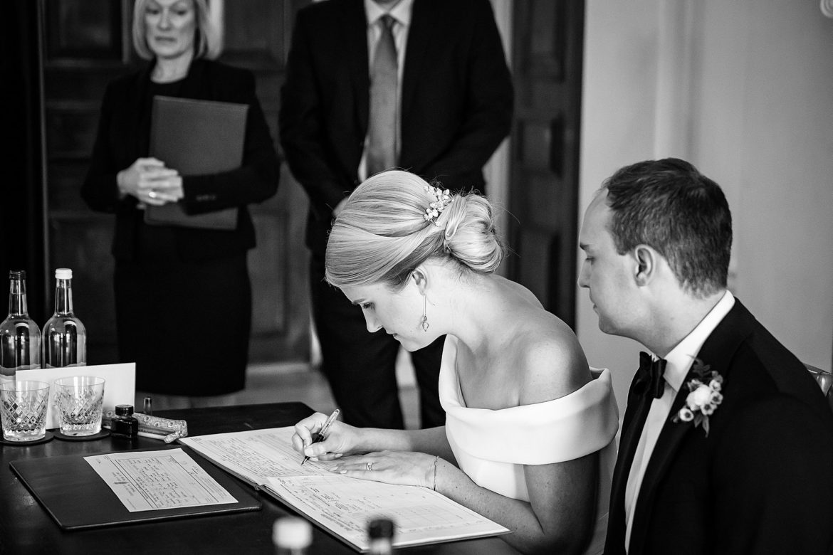 The bride and groom sign the marriage register at The Ned