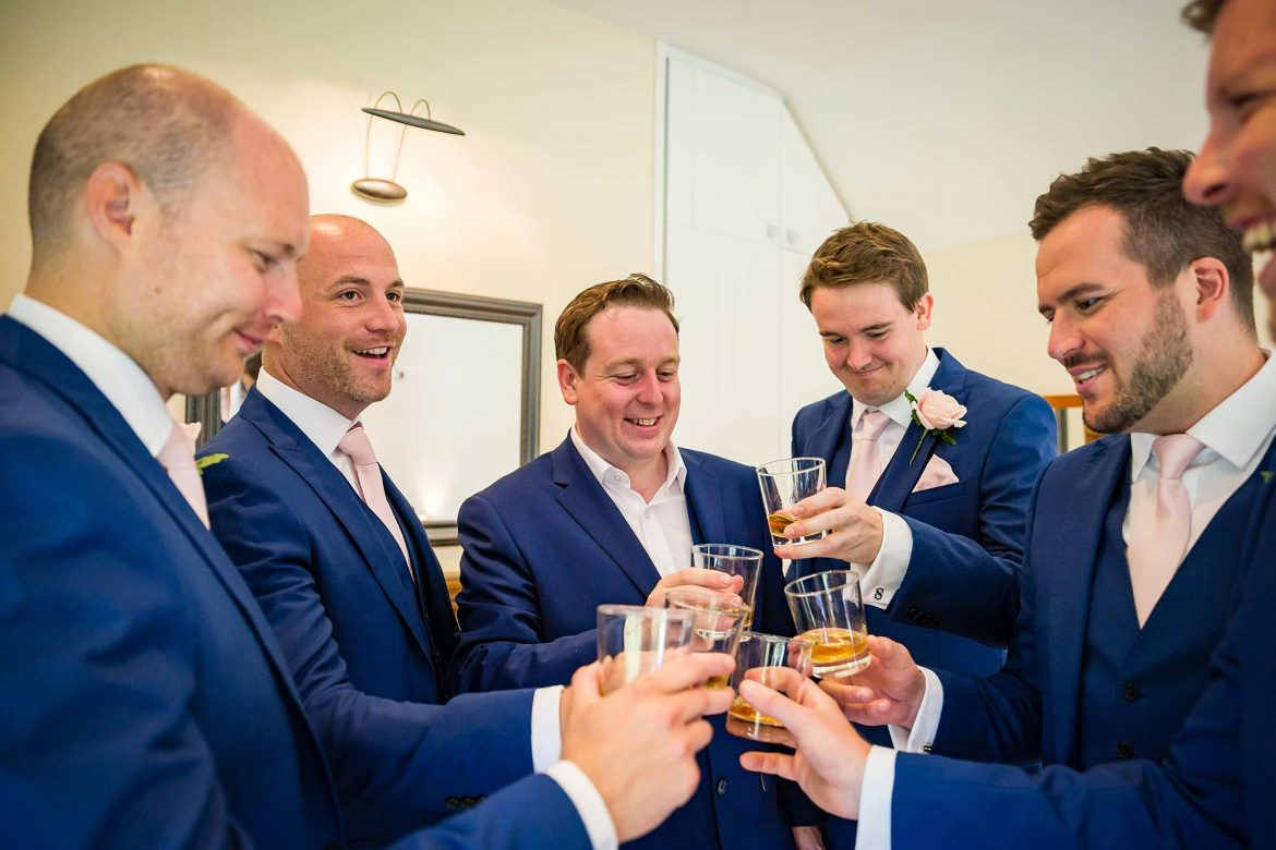 guys toast with whisky before the wedding