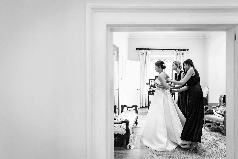 bridesmaids do up brides dress