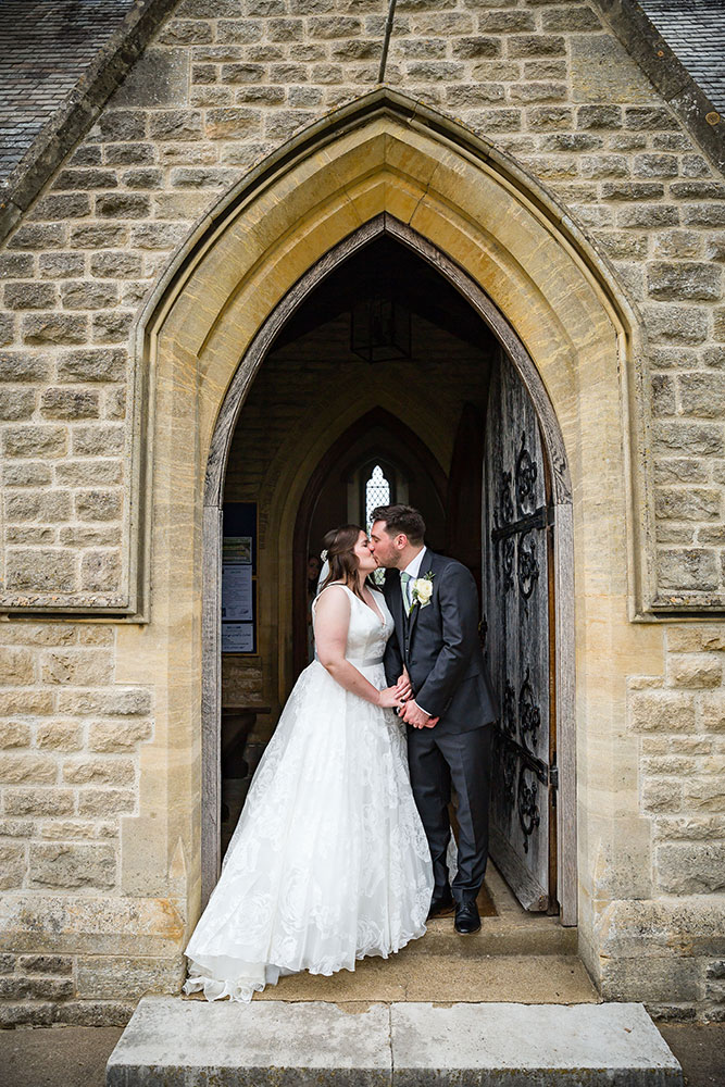 they kiss under an archway
