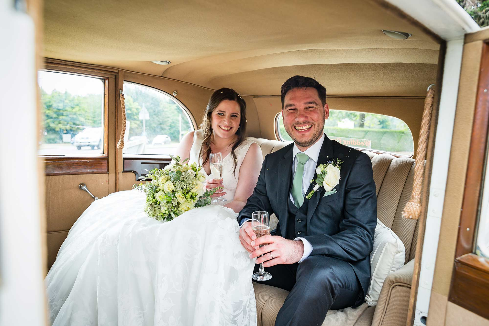 the bride and groom in their wedding car going to Brocket Hall