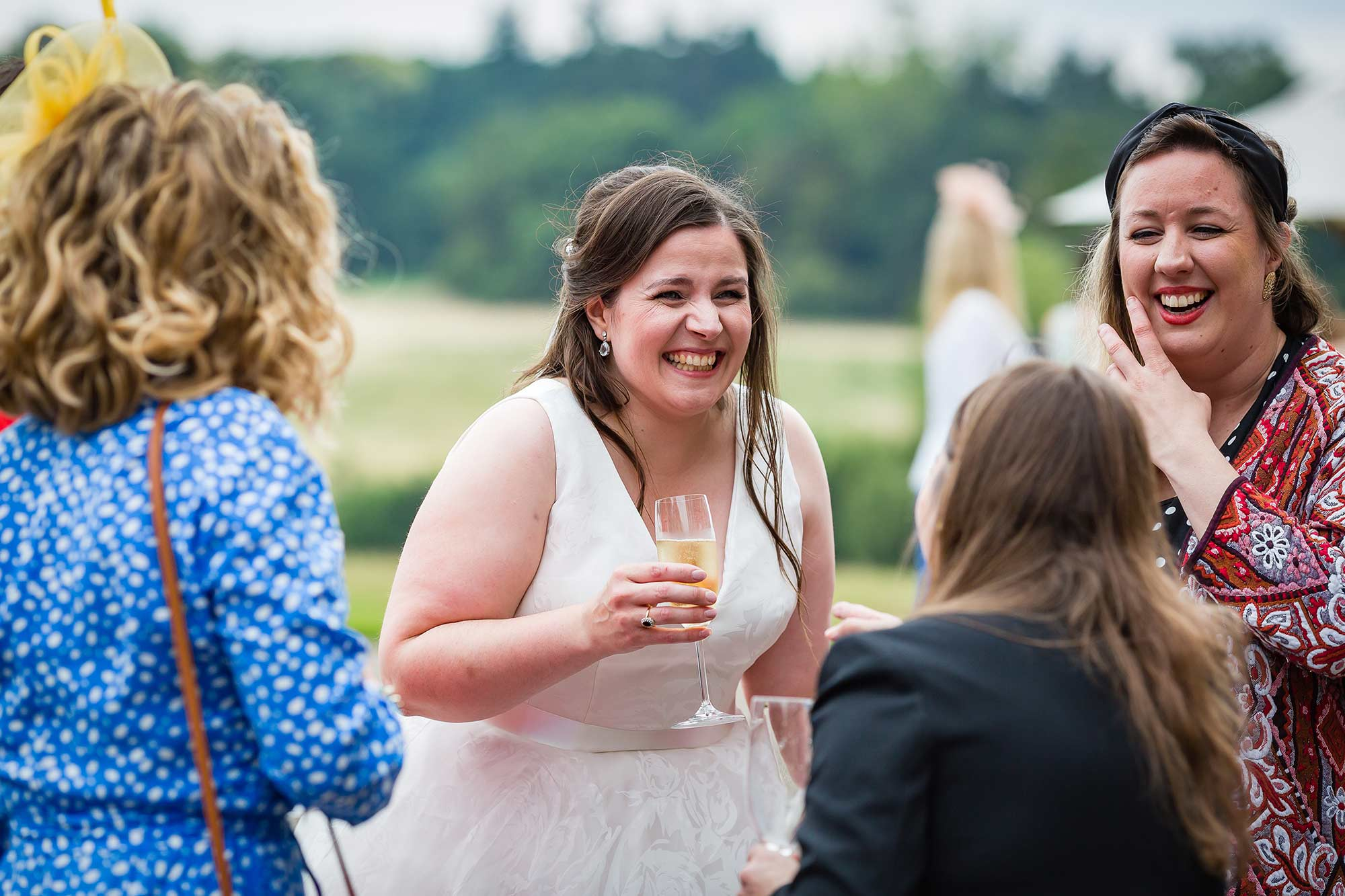 bride drinks chamapne and laughs